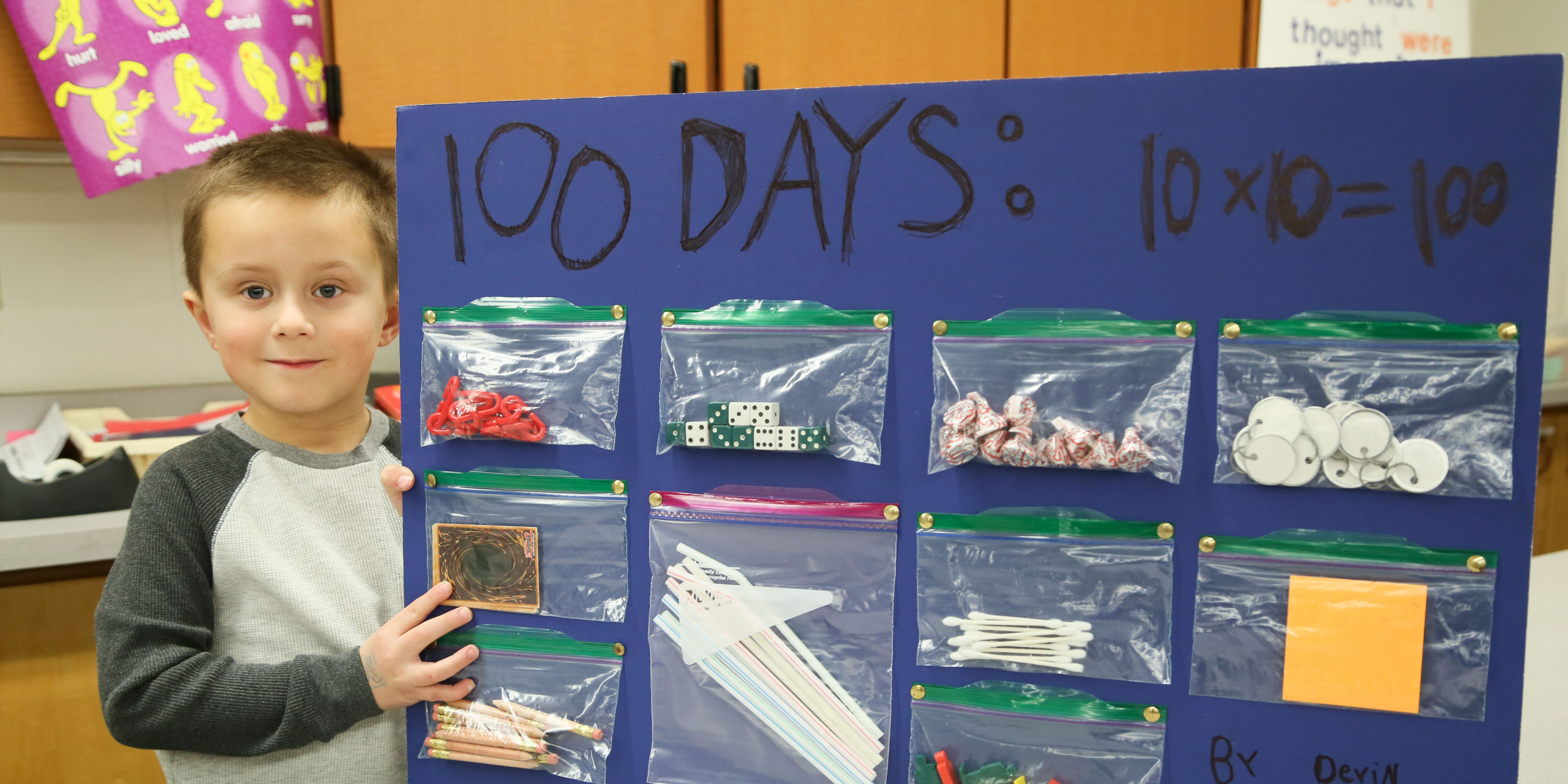 Boy stands with board of 100 things to celebrate 100th day of school.