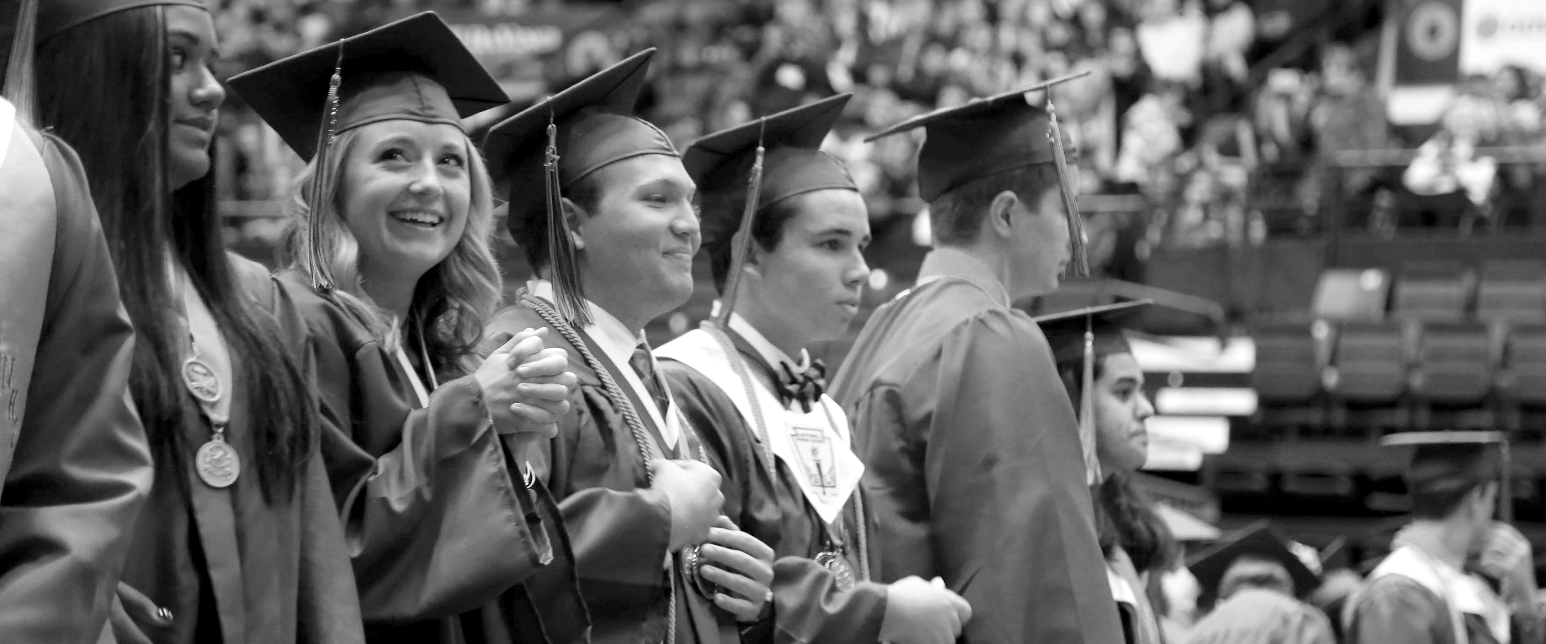 High school seniors in caps and gowns smiling before graduation