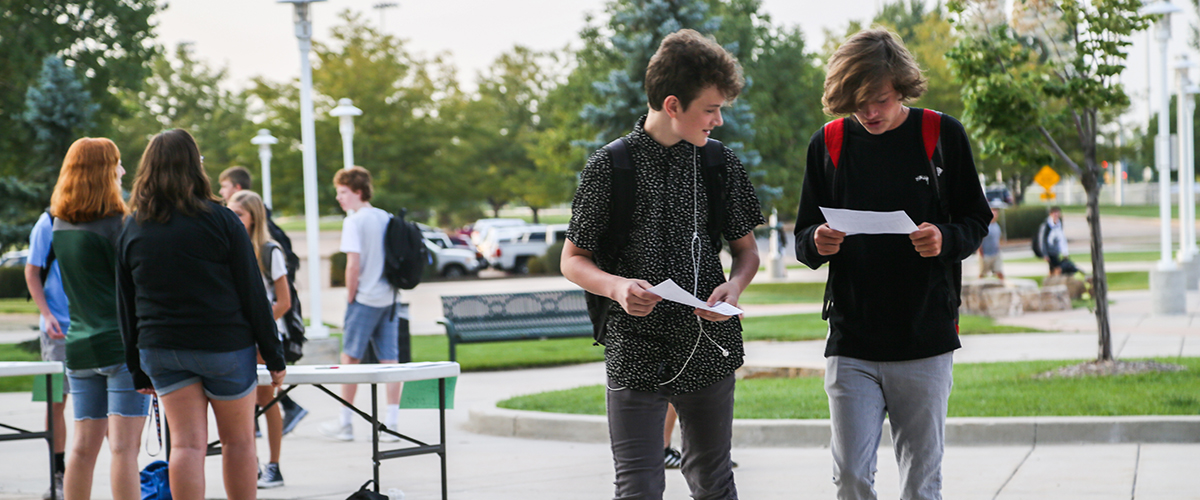 Two freshmen boys compare schedules walking into Fossil Ridge High School.