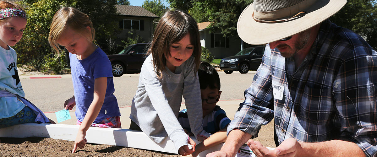 Students plant seeds in a school learning garden.