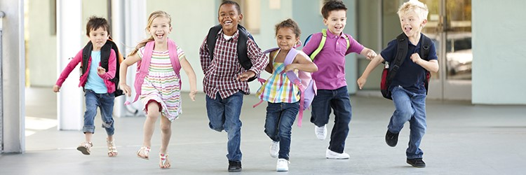 Young elementary students skipping in a bright hallway.