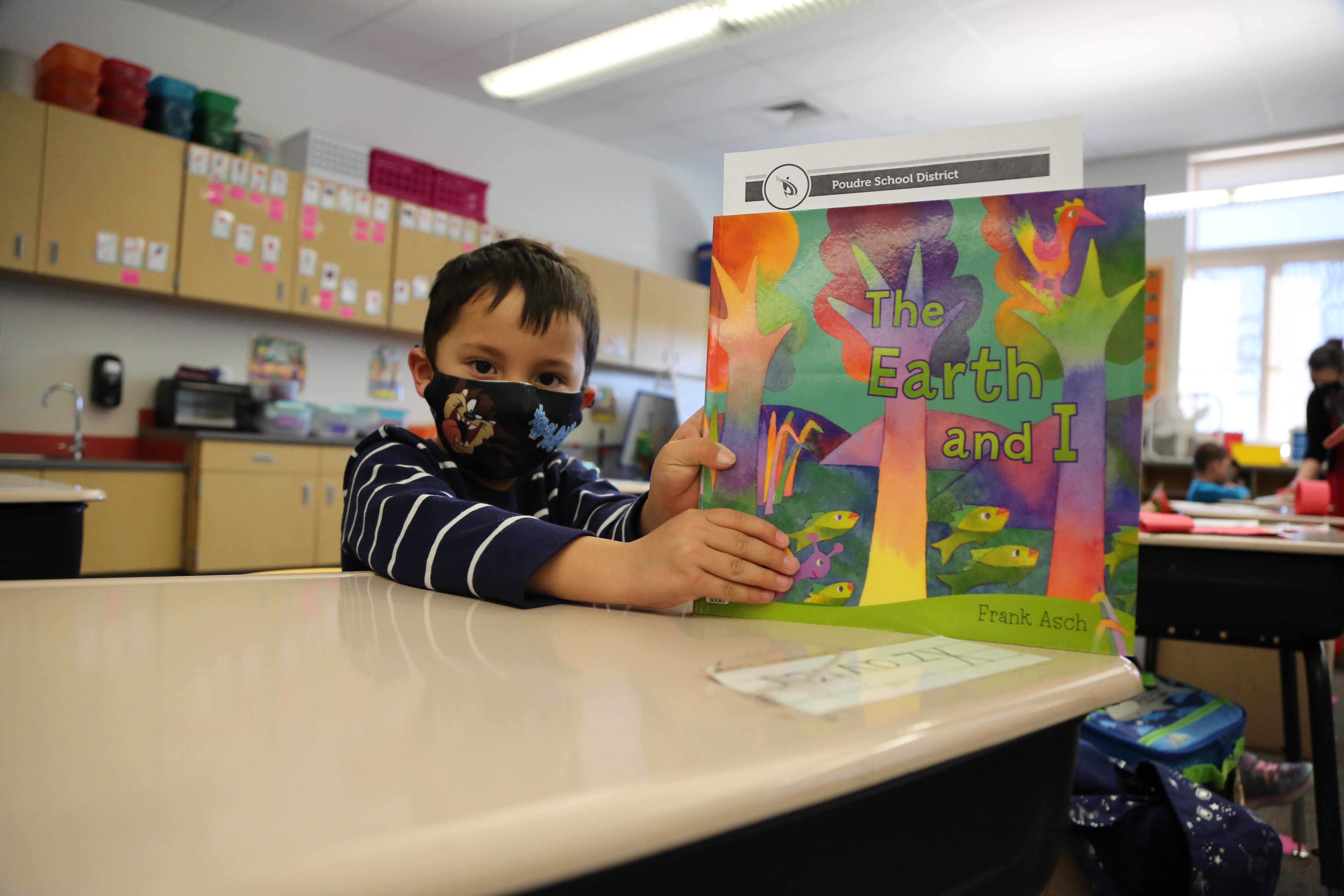 A Rice Elementary student props up his book.