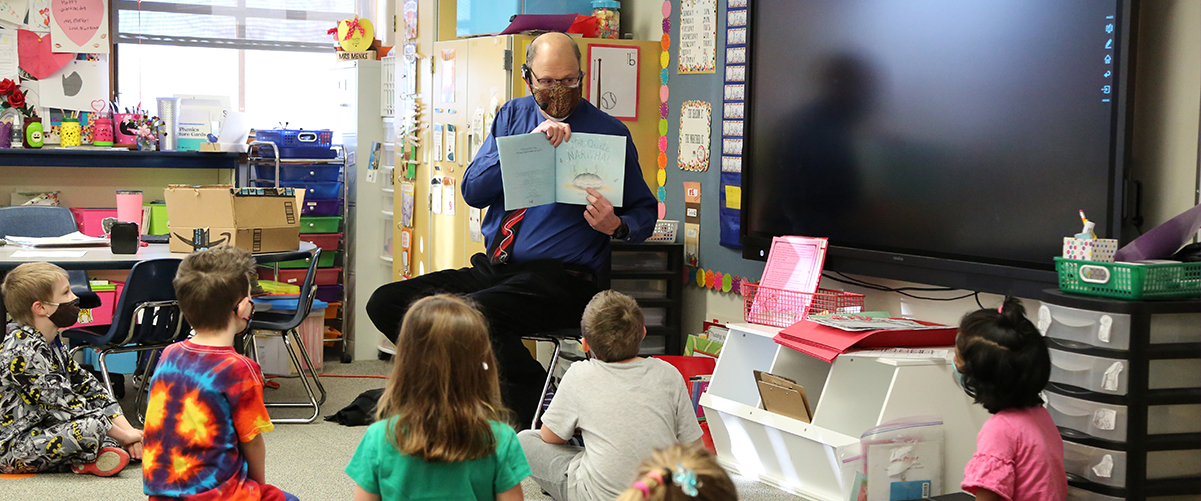 A PSD Board of Education member reads to kids.