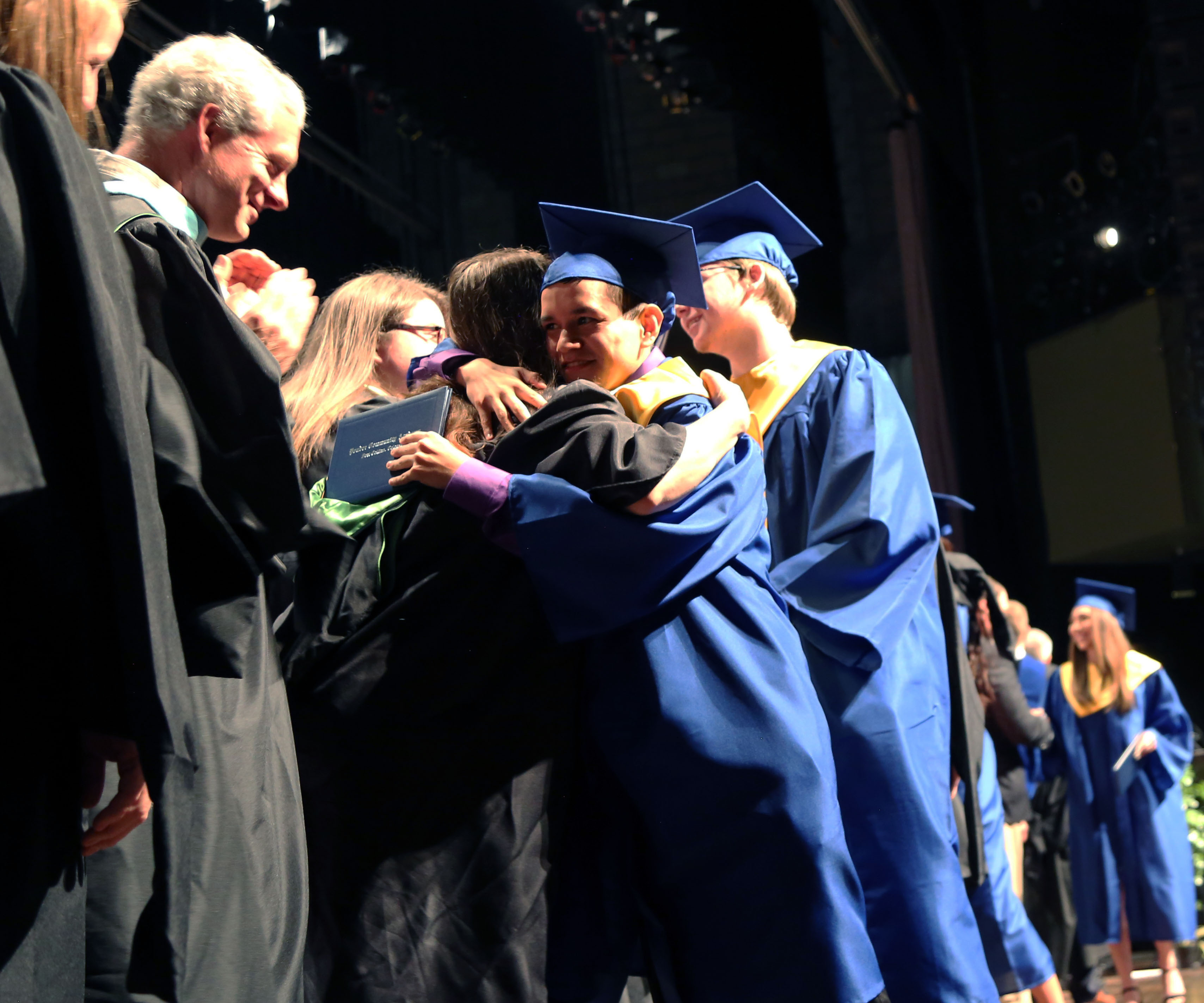 PCA graduates hug with their diplomas