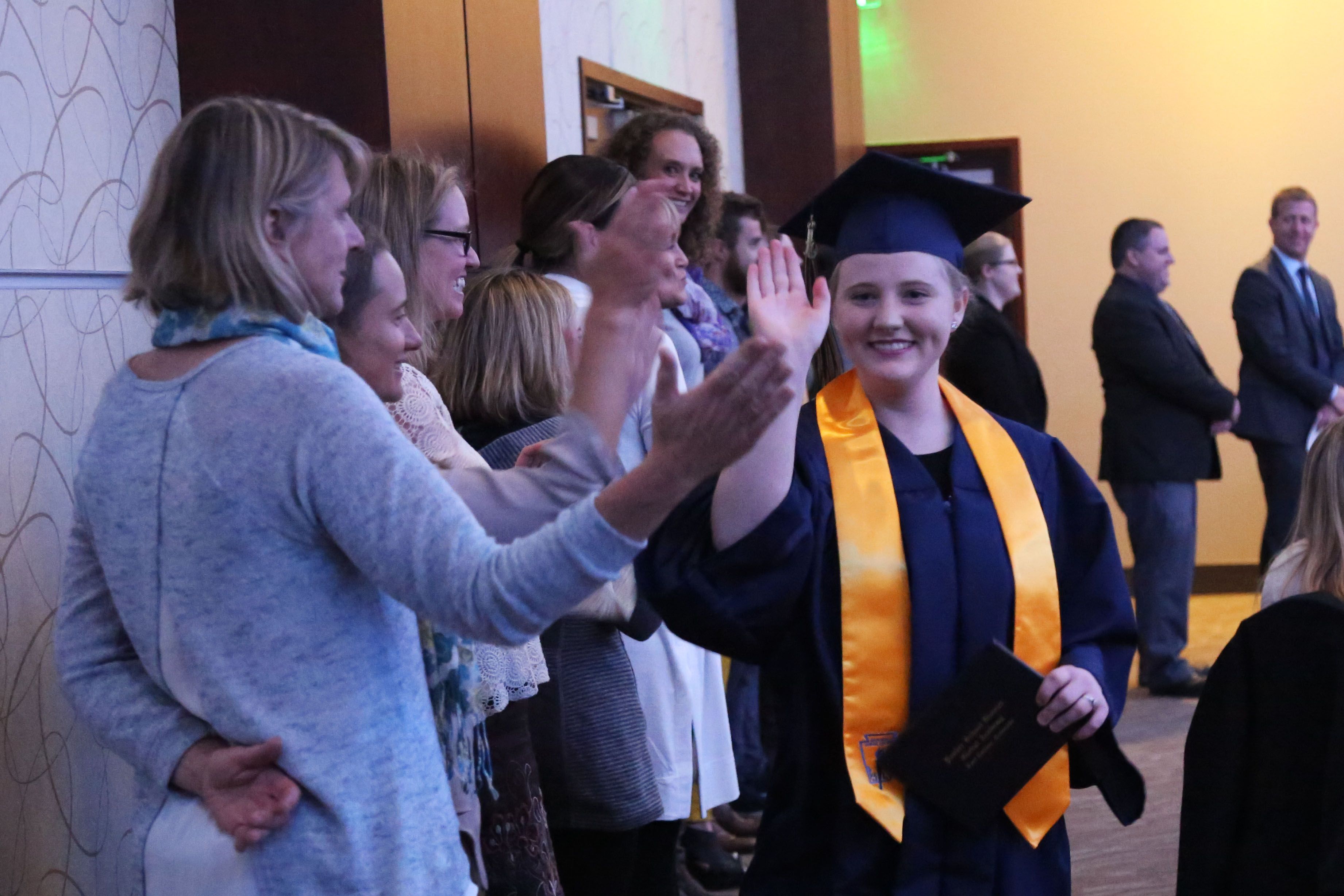 A graduate offers high fives down a reception line.