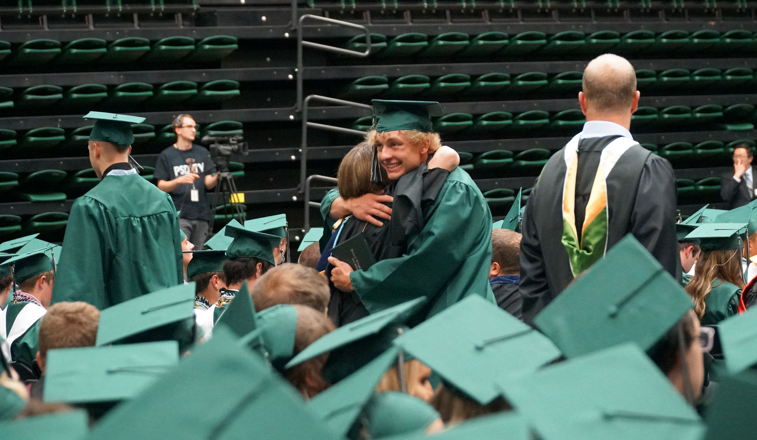 Two Fossil Ridge grads hug in a sea of graduates.