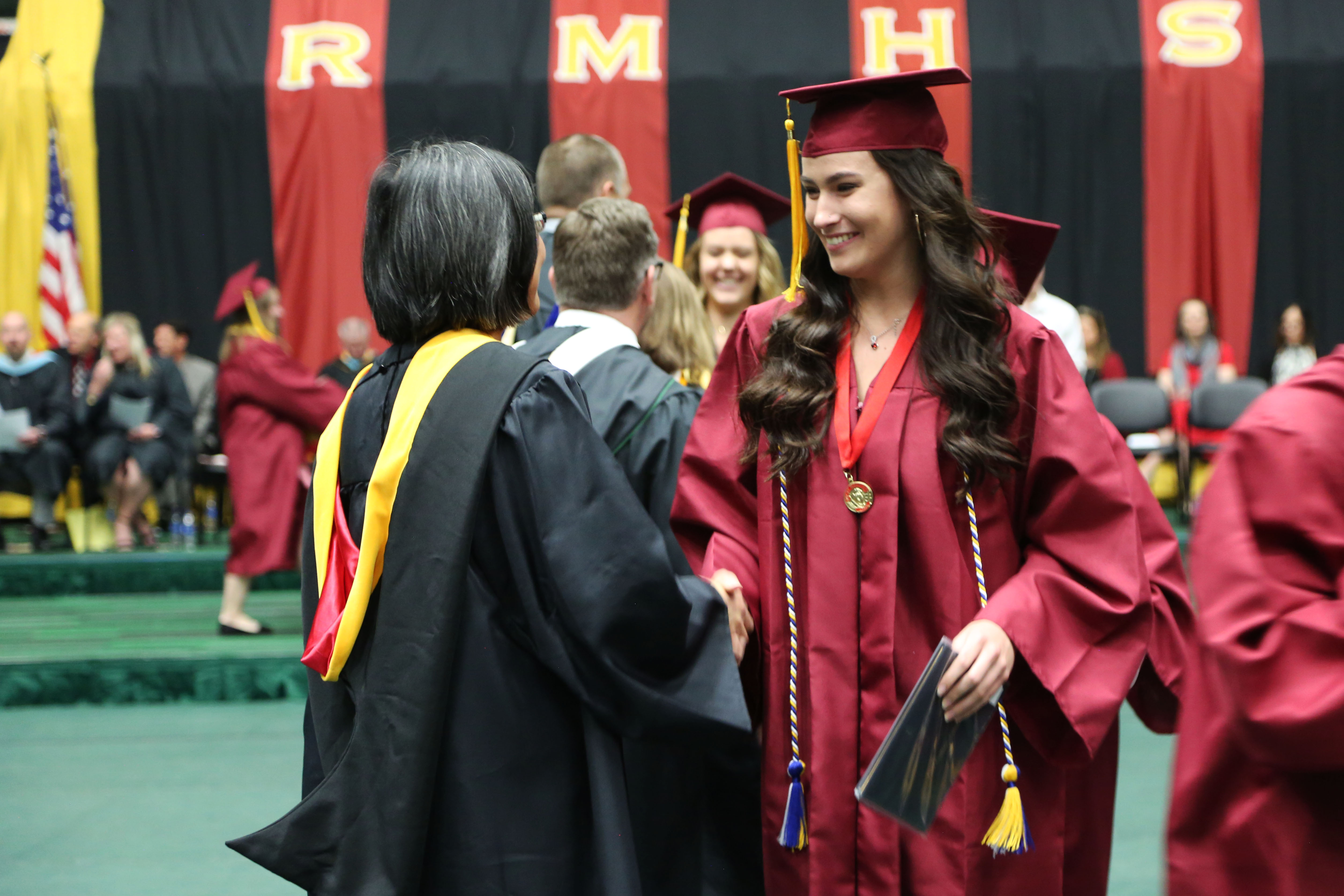 A Rocky graduate talks with her teacher.