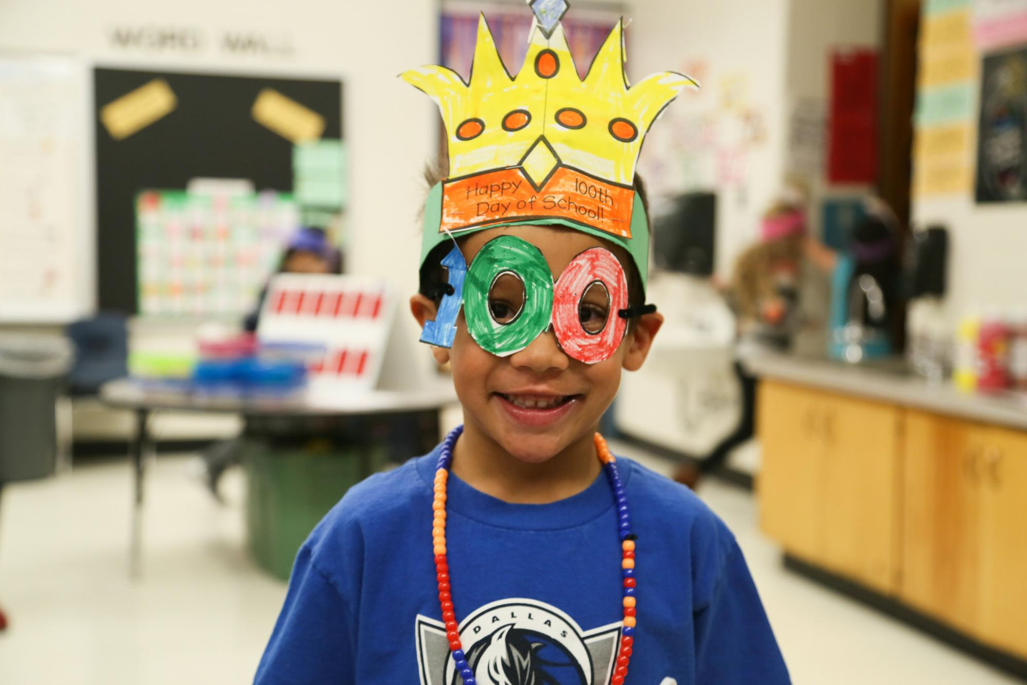 Beattie boy wearing a crown and glasses in the shape of 100 to celebrate 100 days of schools.