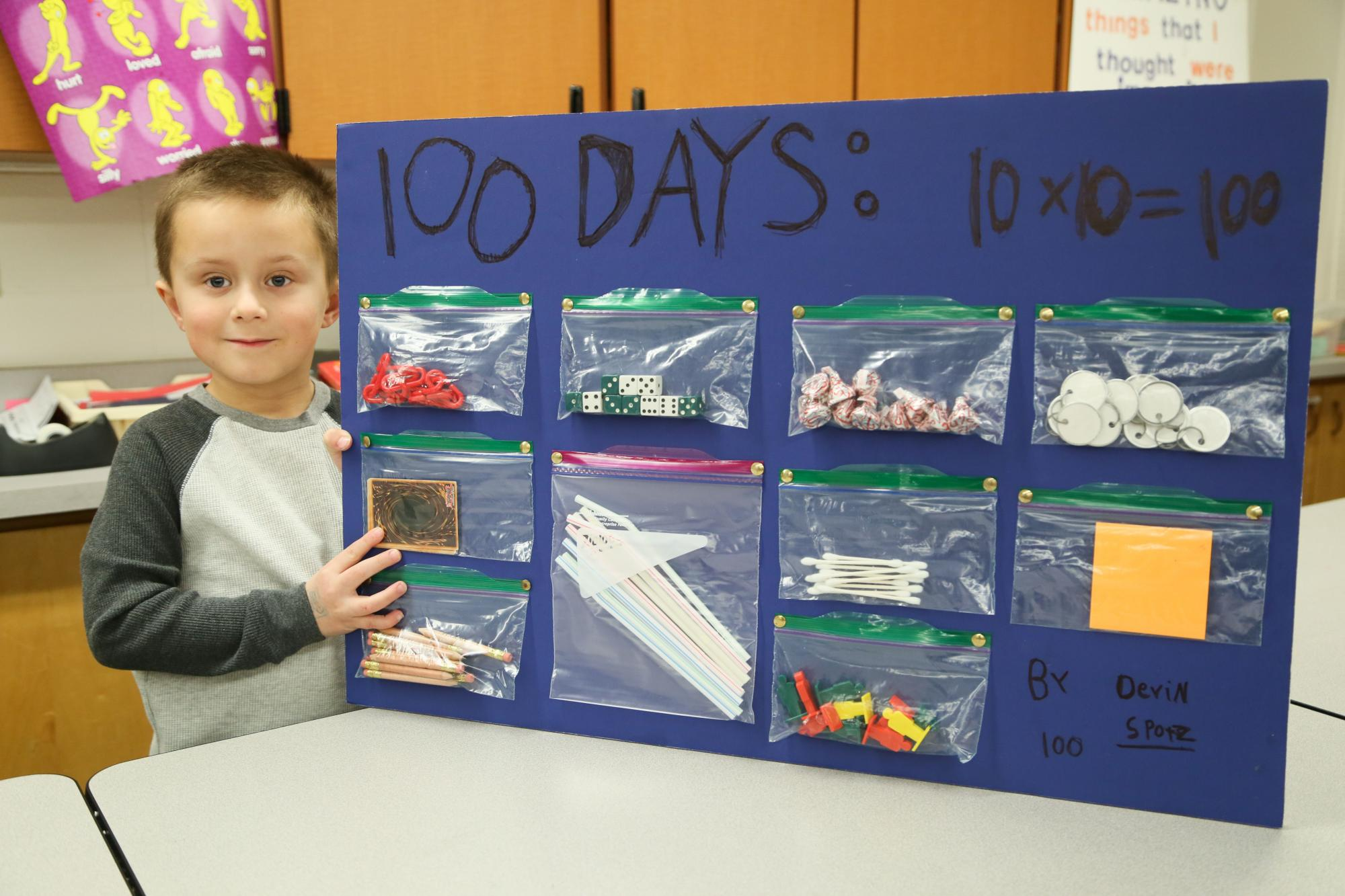 Beattie boy stands with his board of 100 things to celebrate 100 days of school.