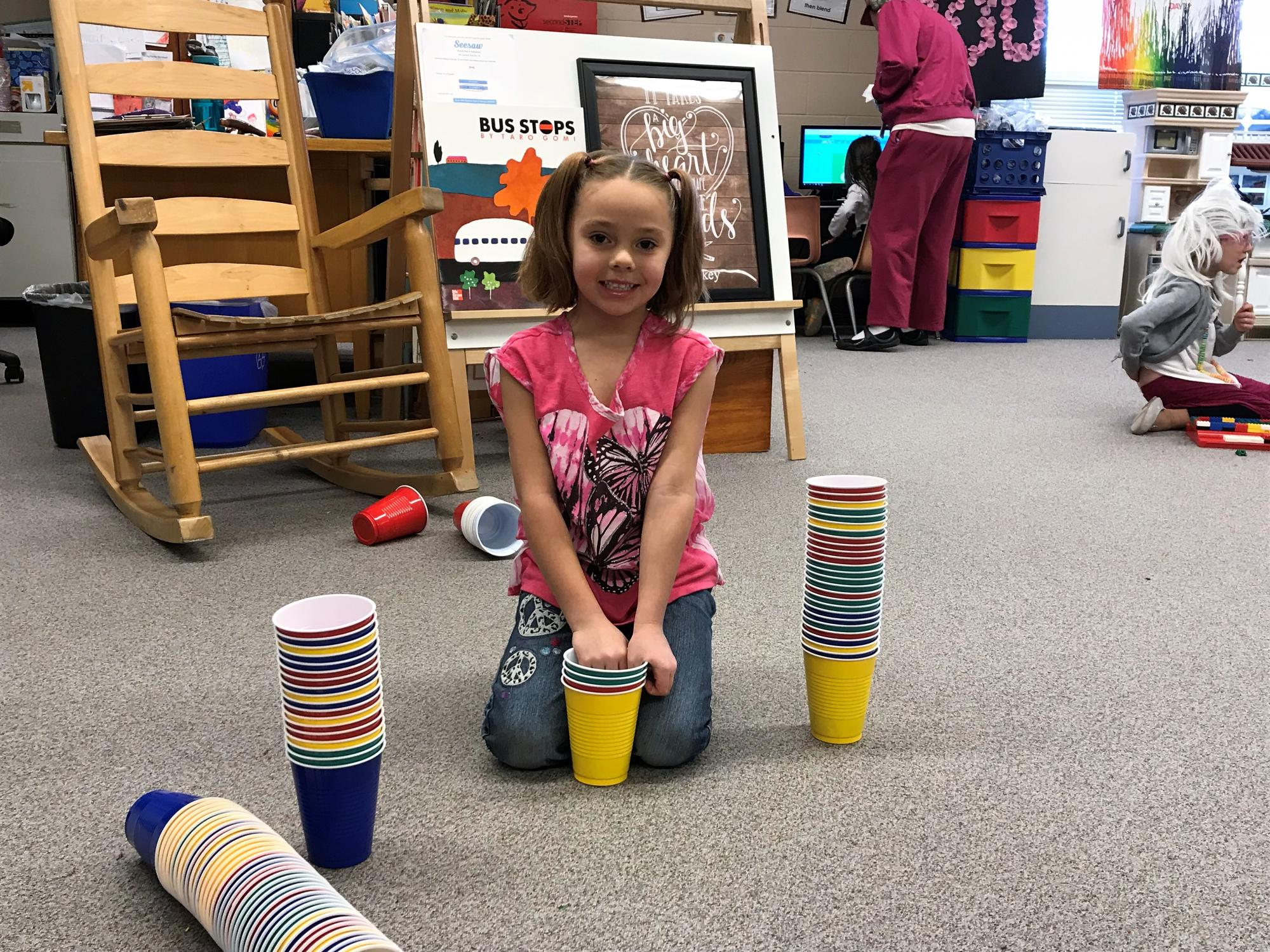 A young girl kneeling on the floor with 100 plastic cups.
