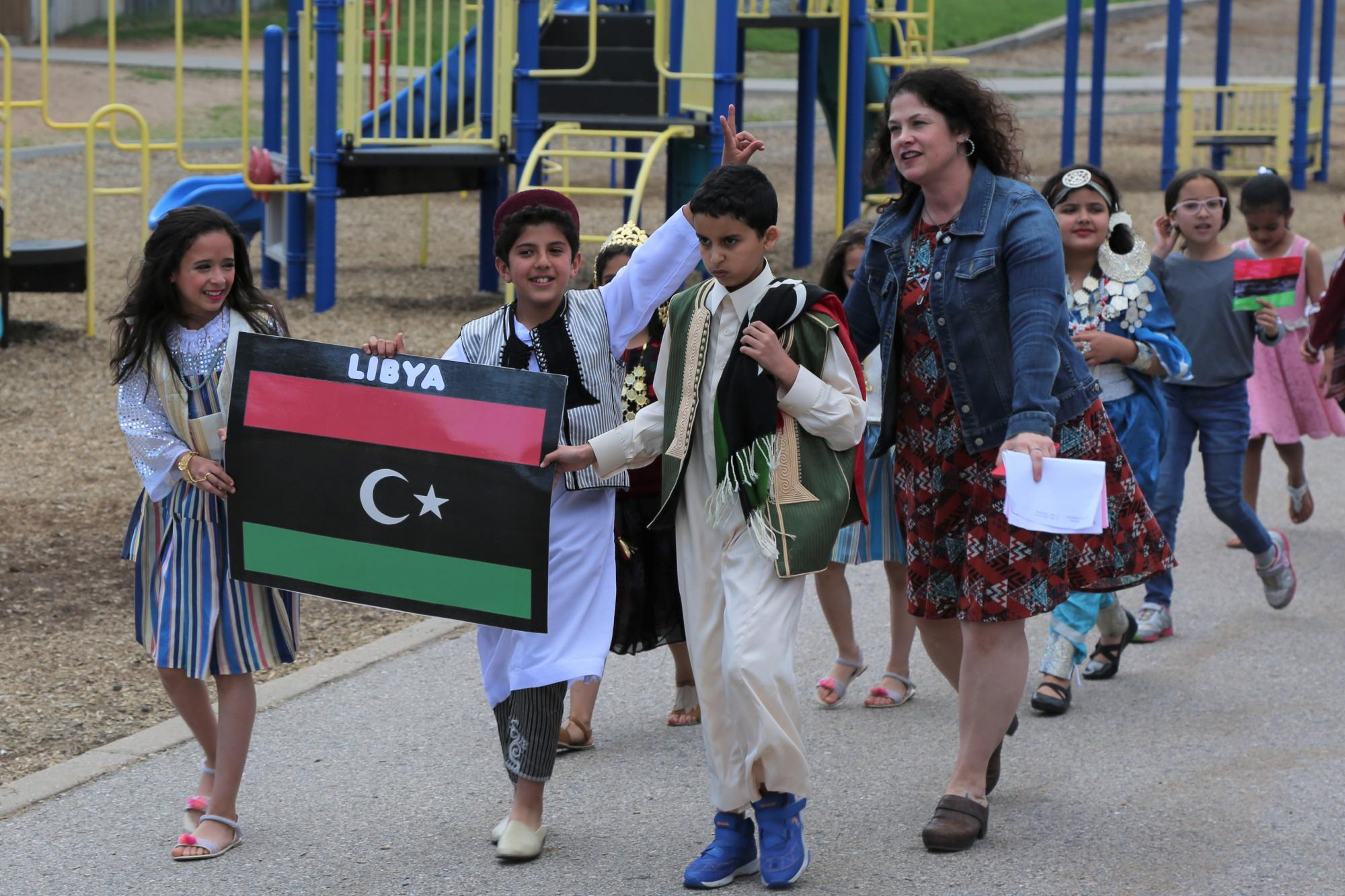 A group of elementary students wearing cultural dress walk in a parade outside.