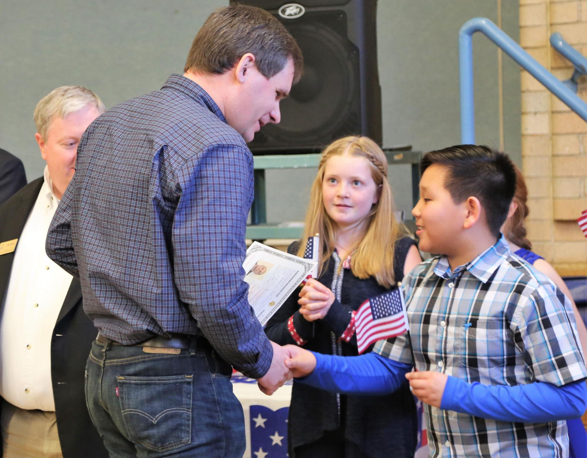 A Dunn student presents a miniature flag to a new citizen.