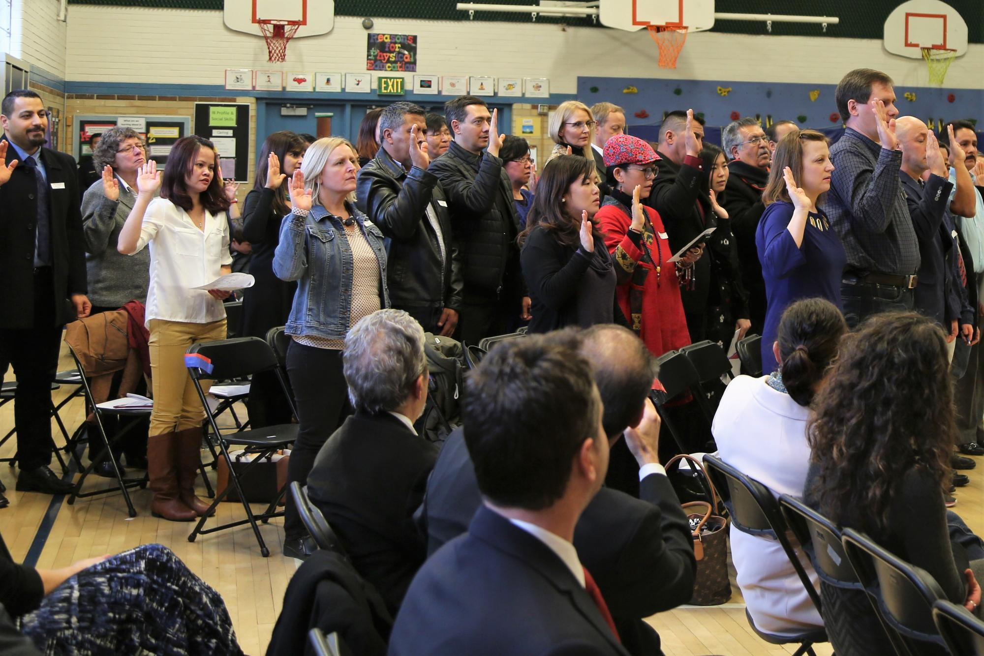 A group of people at Dunn Elementary taking the Oath to become new citizens.