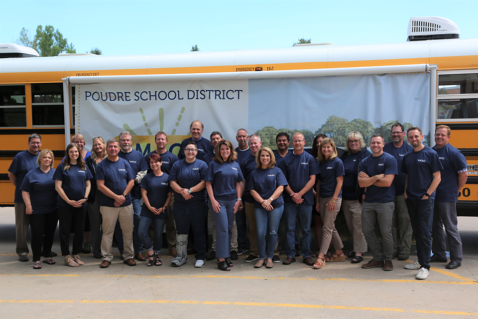 PSD staff who worked on the MAC project pose in front of it.