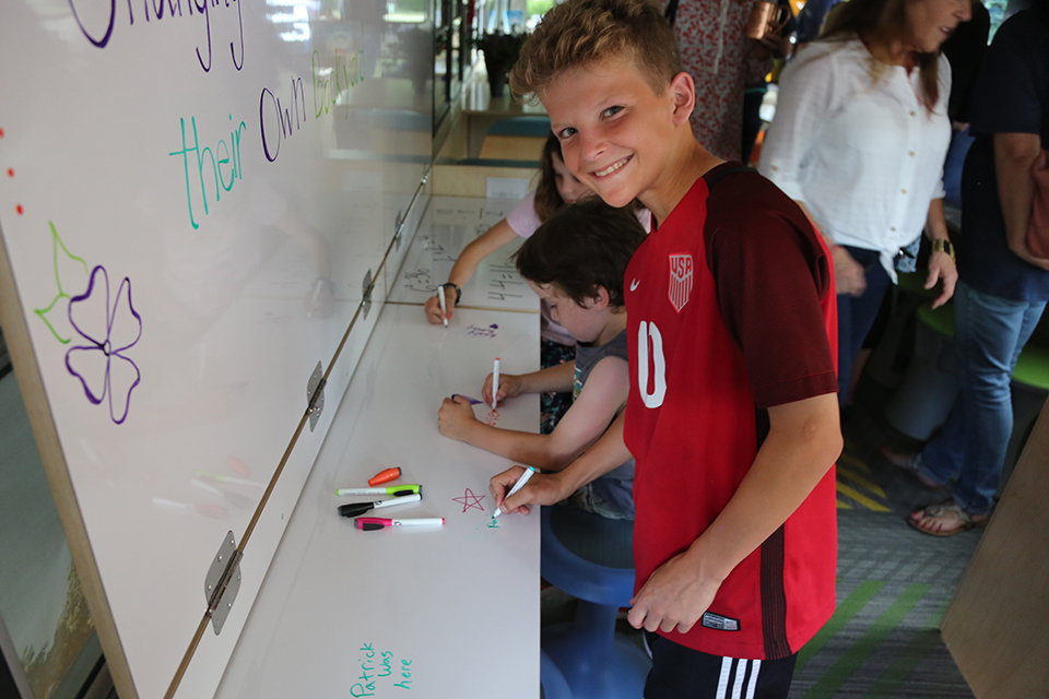 A student works at the white board on the mobile academic classroom.