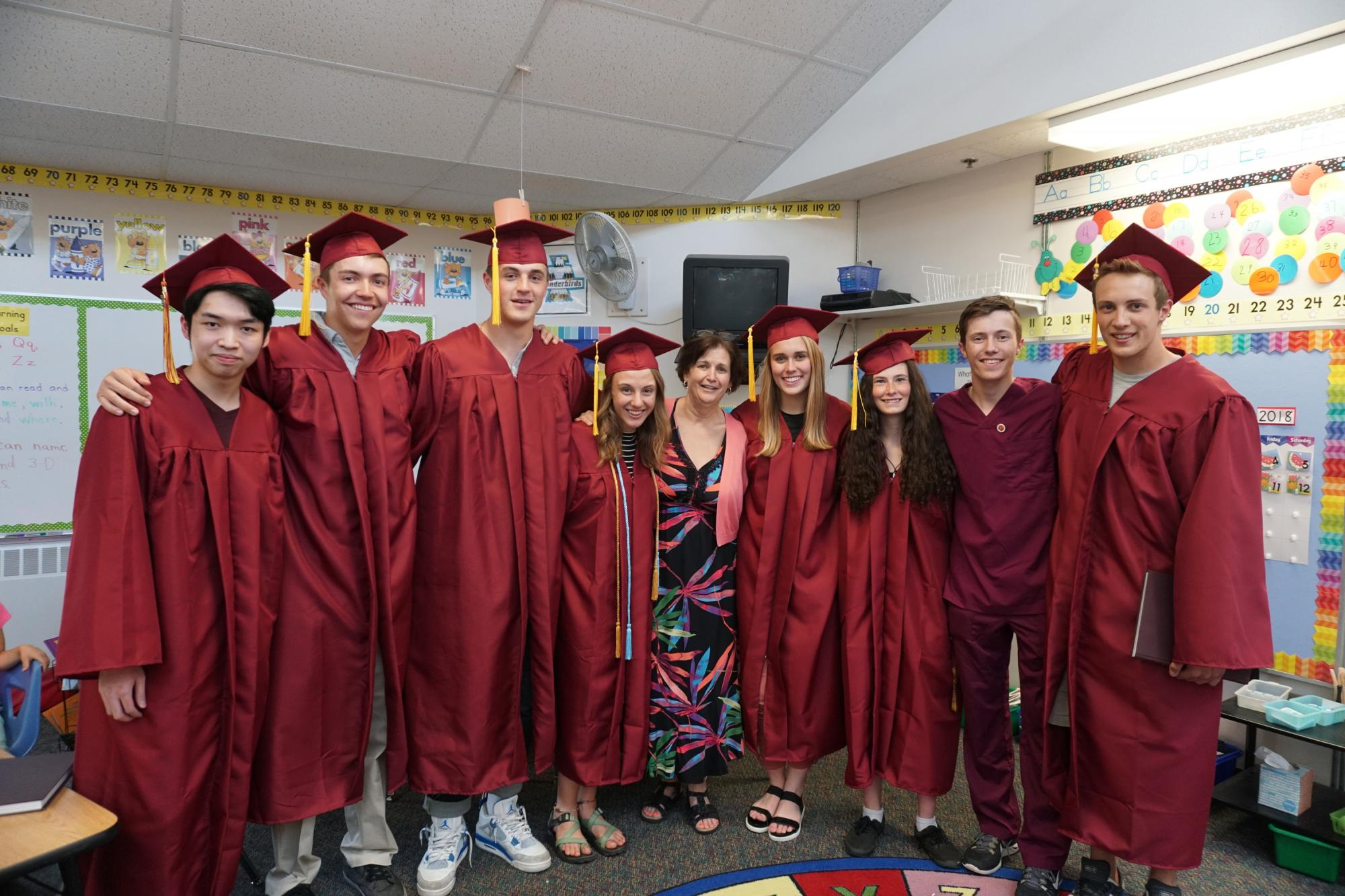 Johnson Elementary kindergarten teacher Lorrie Unrein with a group of former students in high school graduation gowns