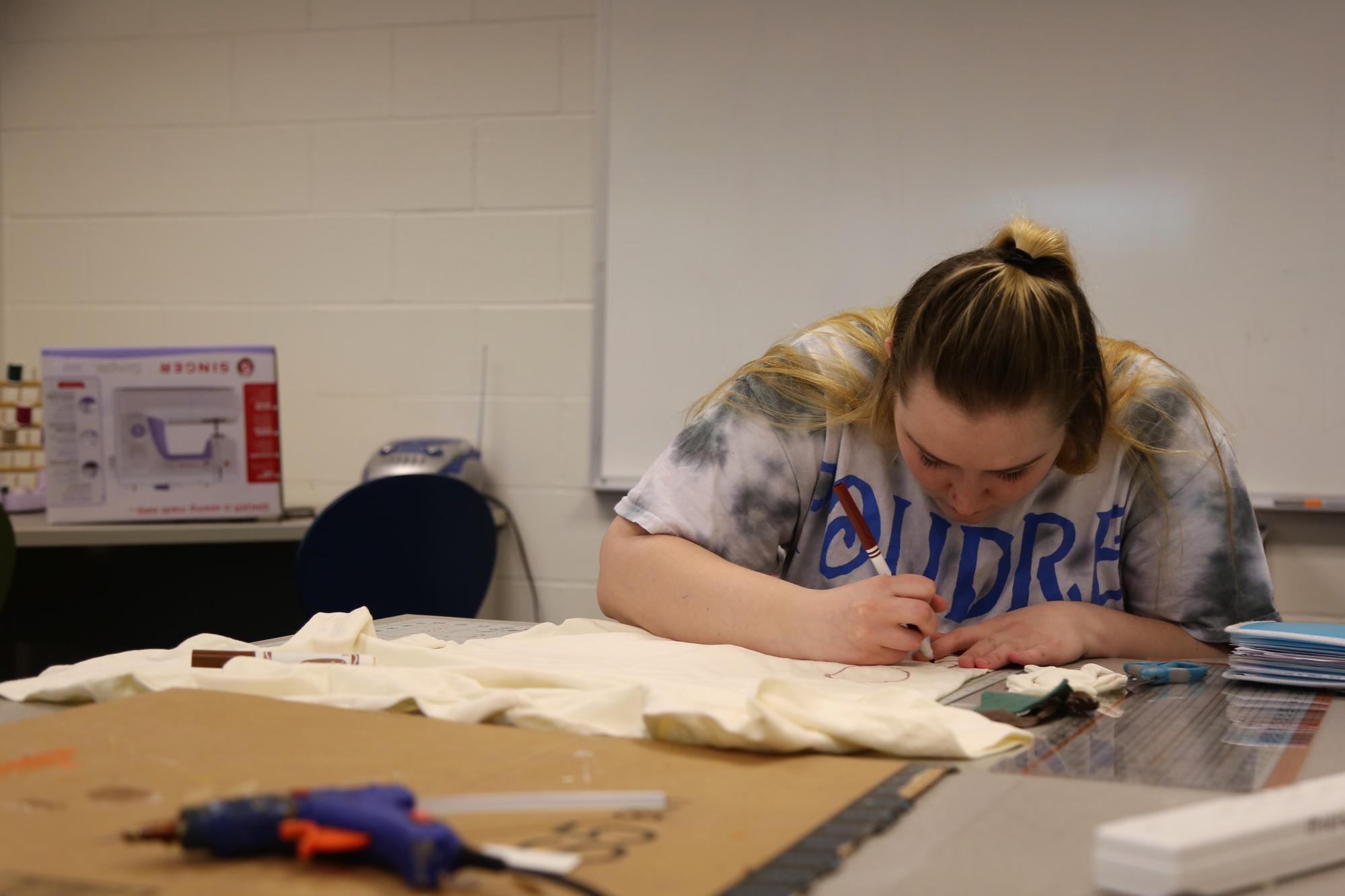 A student decorates fabric with magic markers in the PHS MakerSpace area.