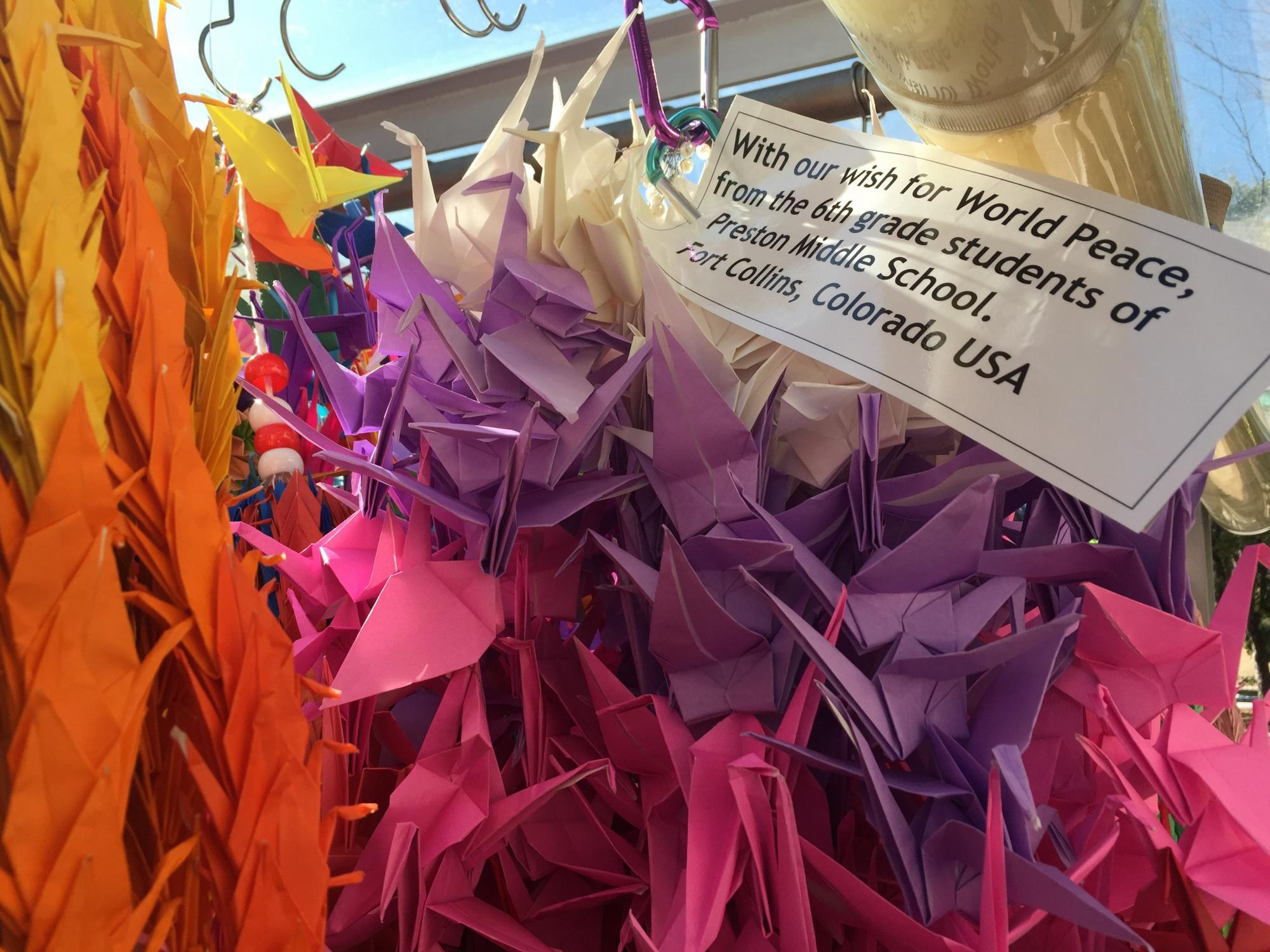 A close up photo of colorful paper cranes with a message of peace from Preston students