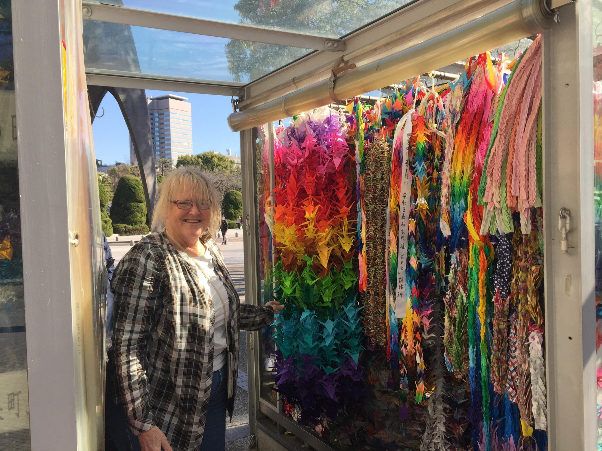 A Preston teacher stands by the folded paper cranes her students made for the Children's Peace Monument