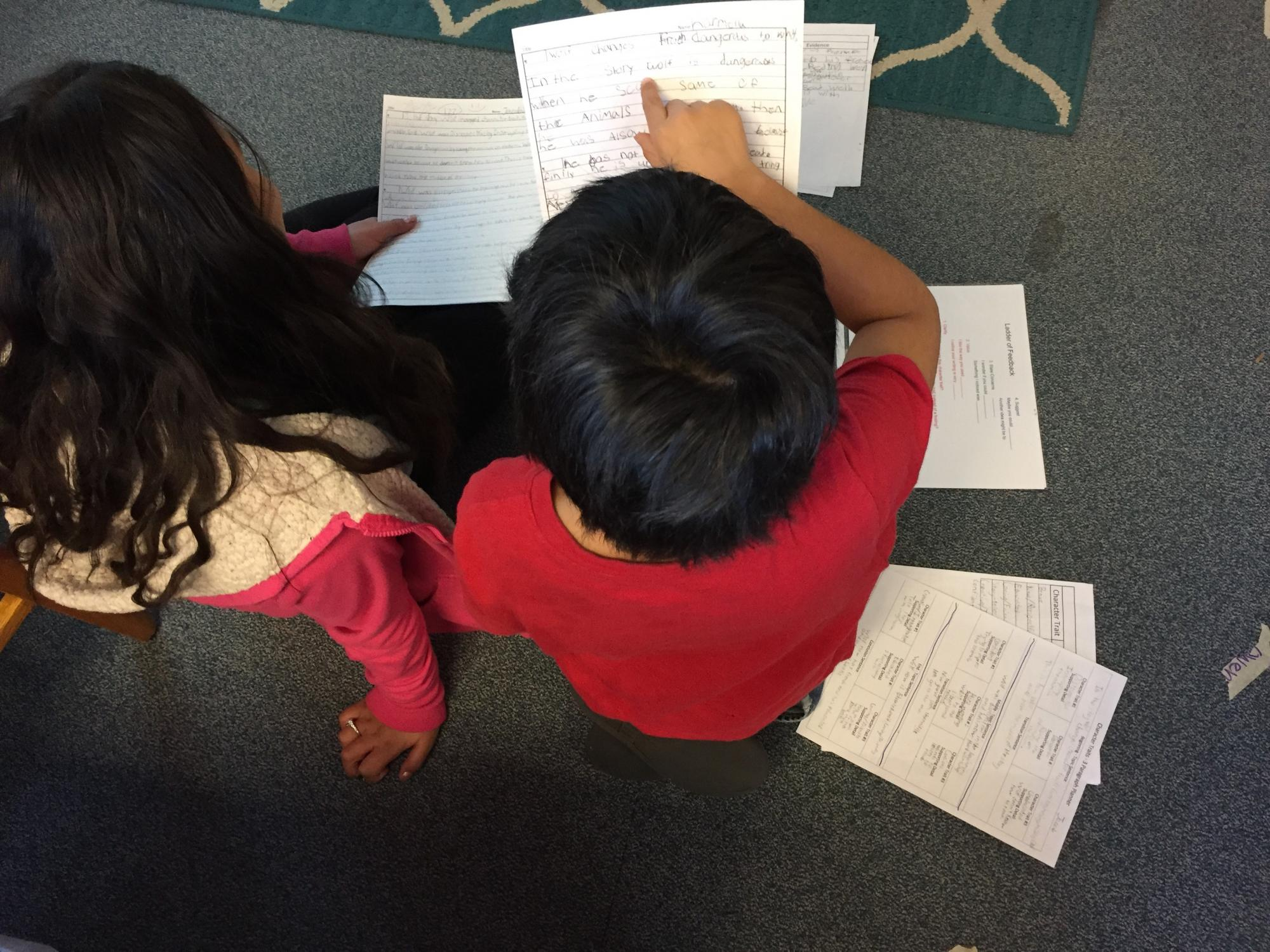 Two kids review work together