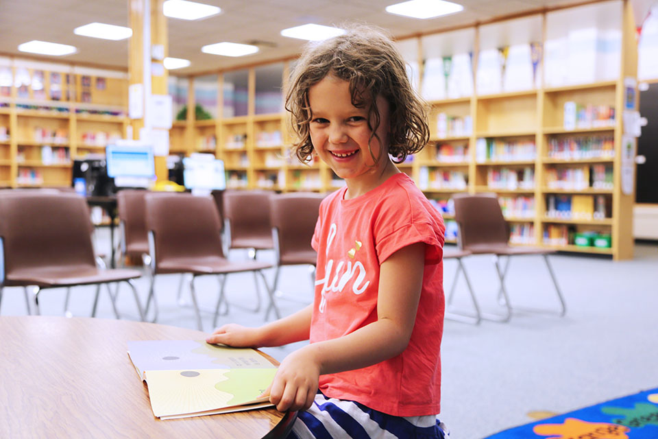 A smiling young girl sits in the library with a book.