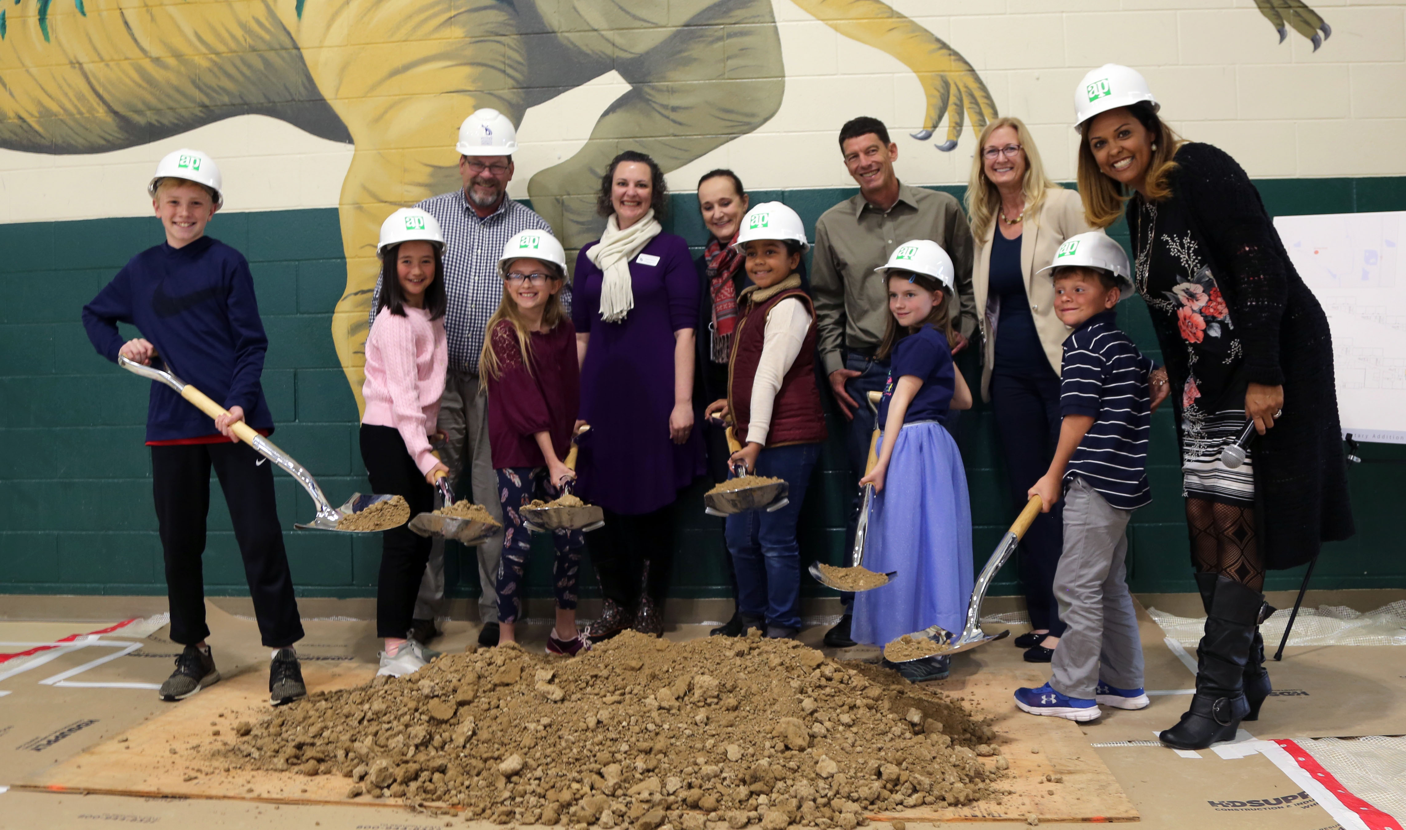 Zach students holding shovels of dirt in the gym as part of the groundbreaking ceremony.