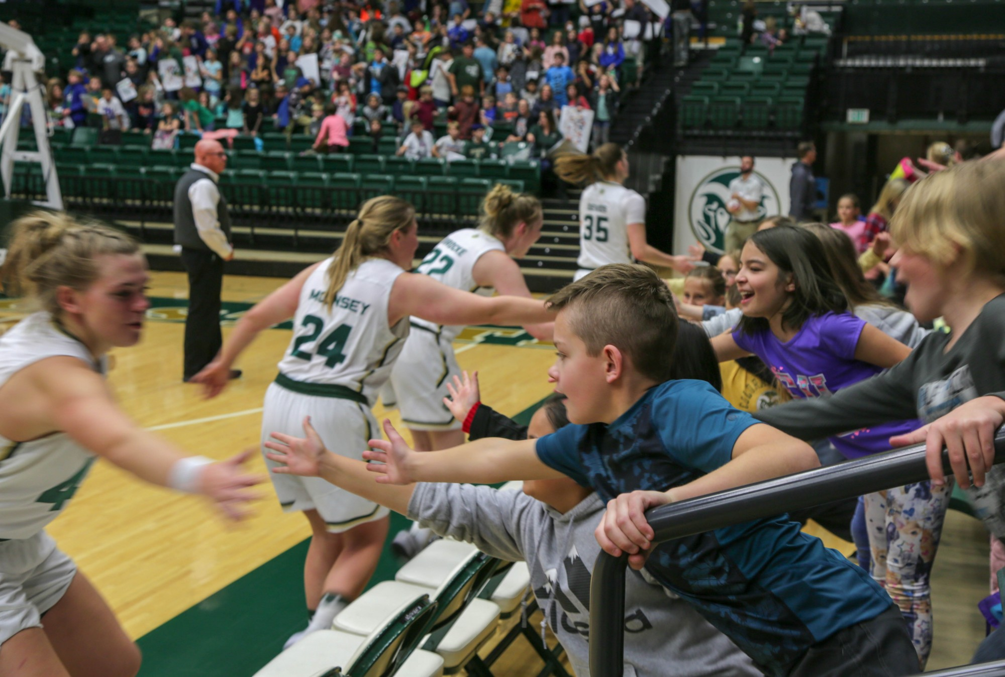CSU women basketball players high five PSD students at the game.