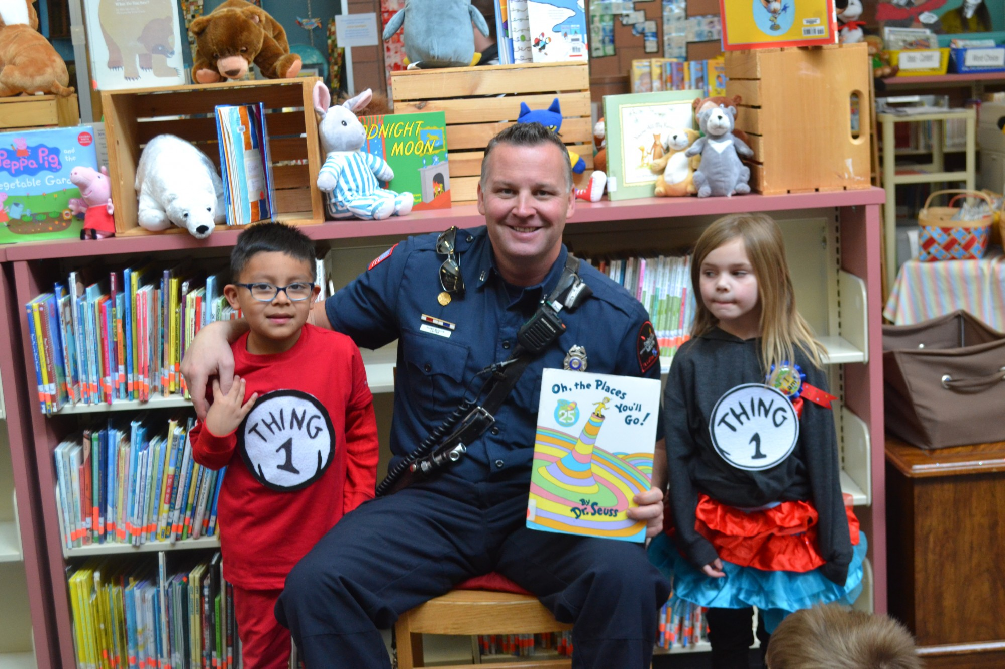 A firefighter reads to a group young students.