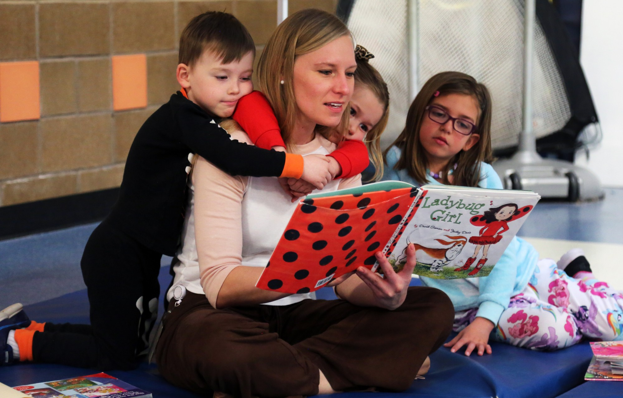 A mom reads to a group of elementary students.