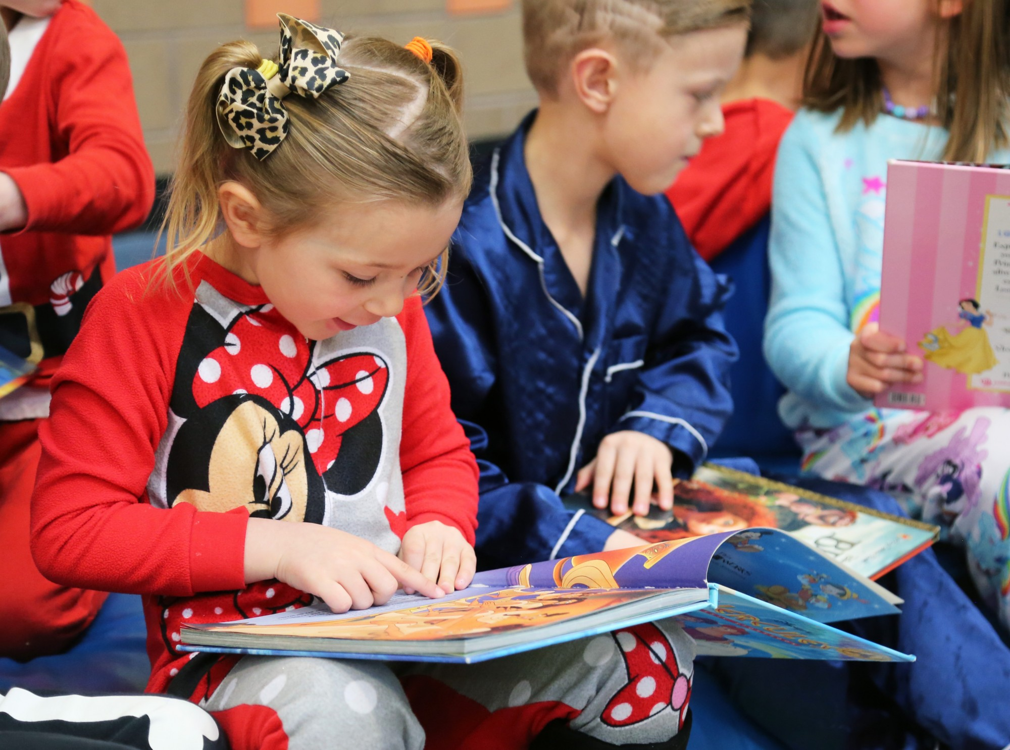 A young girls wearing Minnie Mouse pajamas smiles to herself while reading.