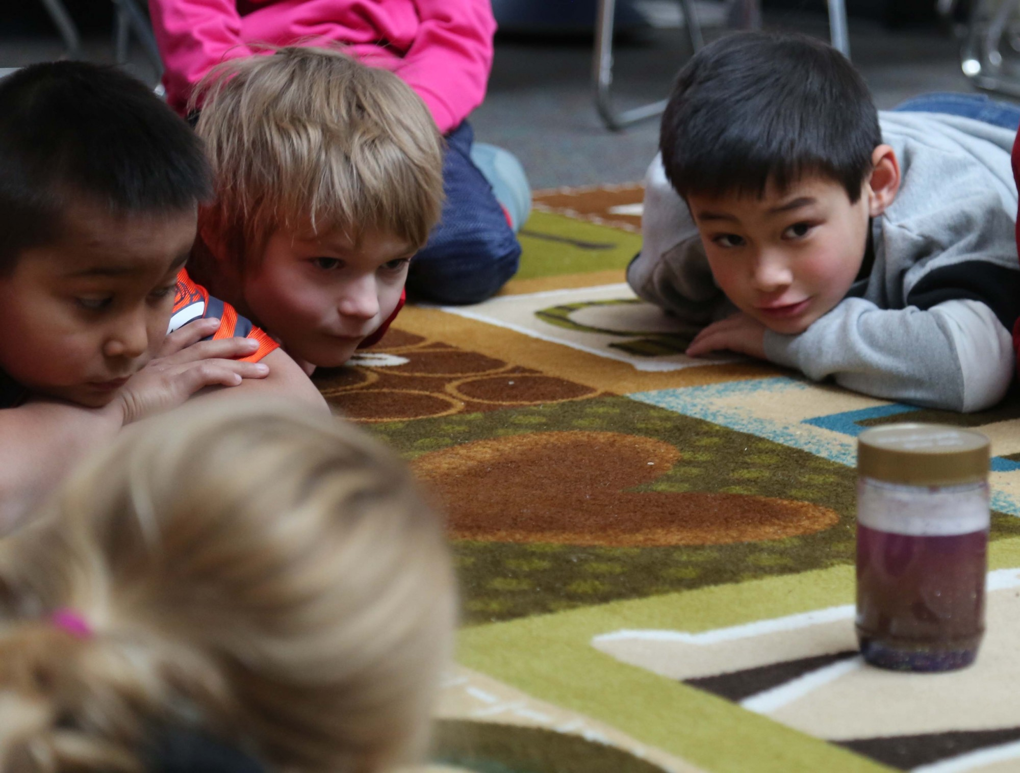 Olander Elementary students lay on the floor looking at a jar with purple glitter.