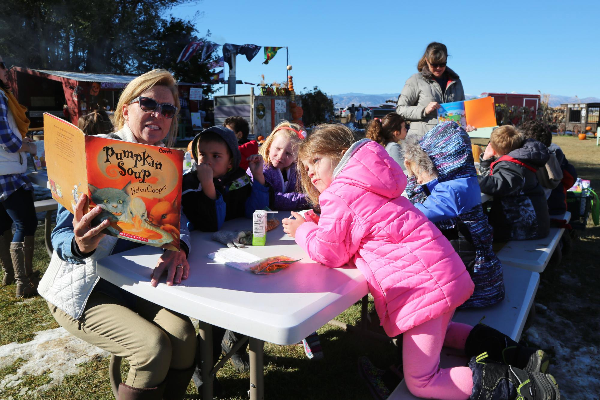 A teacher reads to kindergateners outside during a field trip to a pumpkin patch.