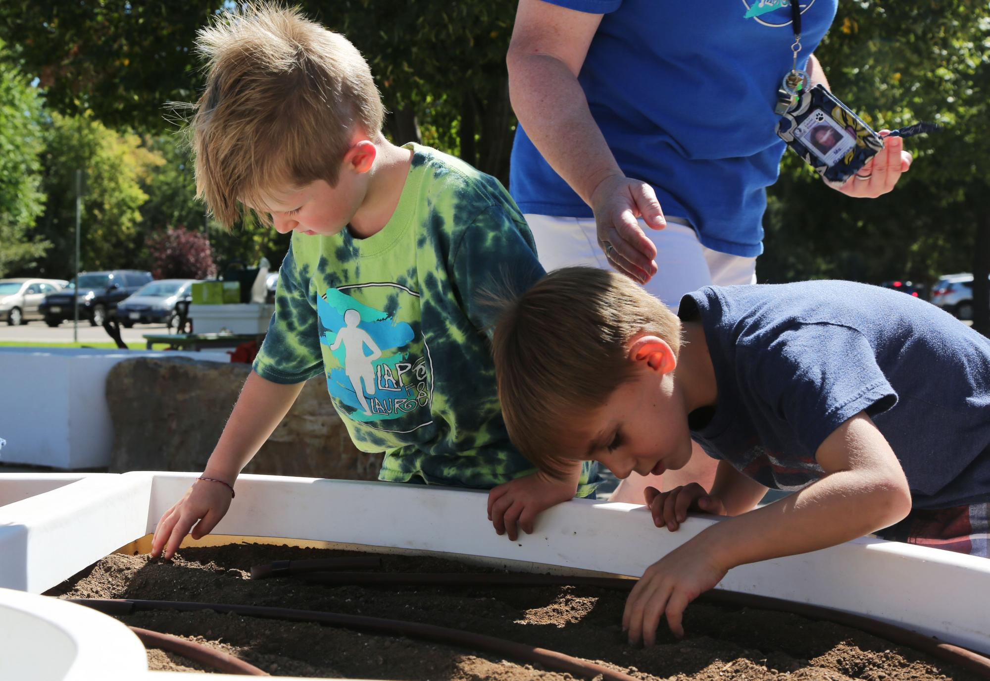 Two boys plant seeds in a school garden bed.