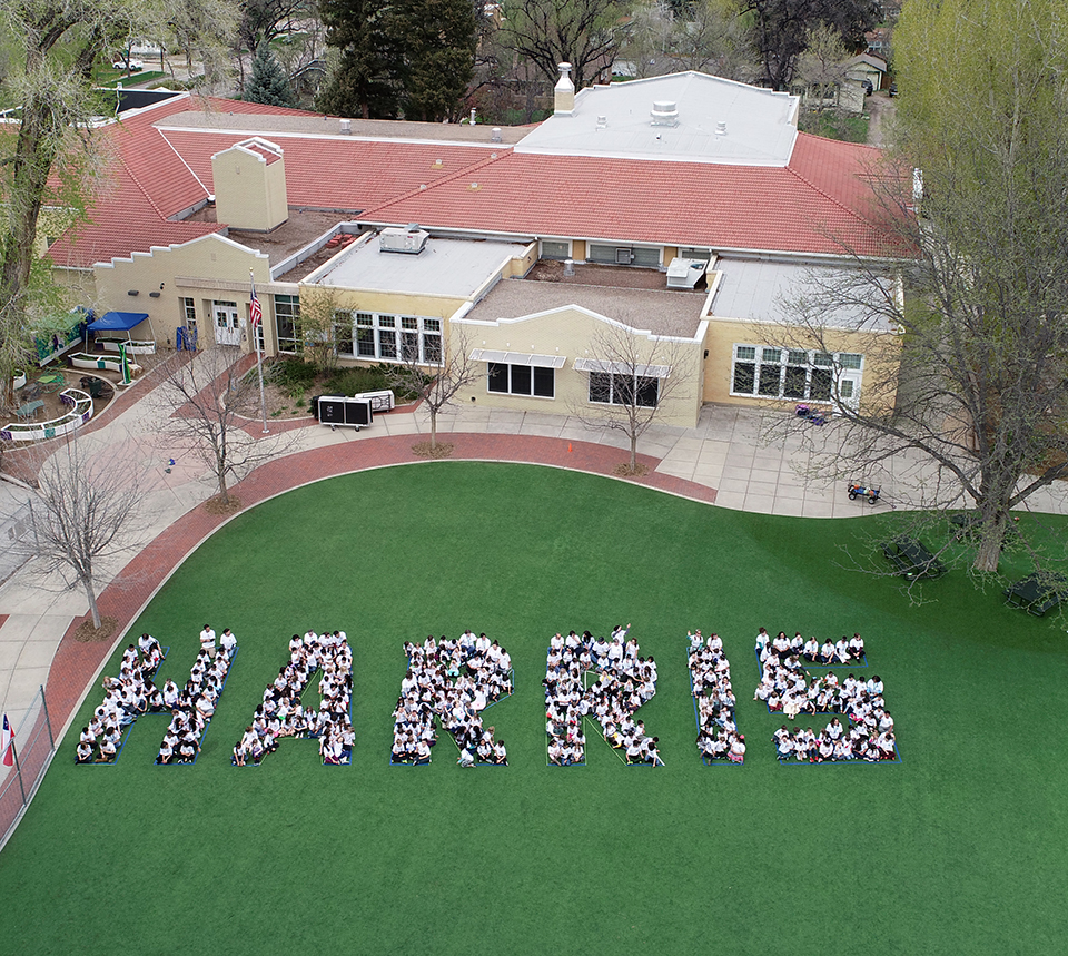 "Drone photo of Harris Elementary community spelling out ""Harris"" on the playground."
