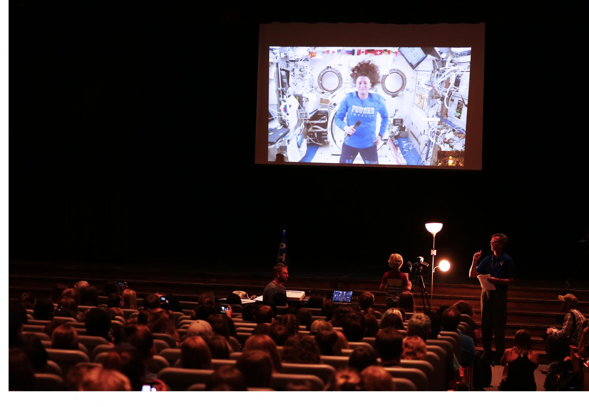 A student asks PHS grad and astronaut a question during a video call to space.