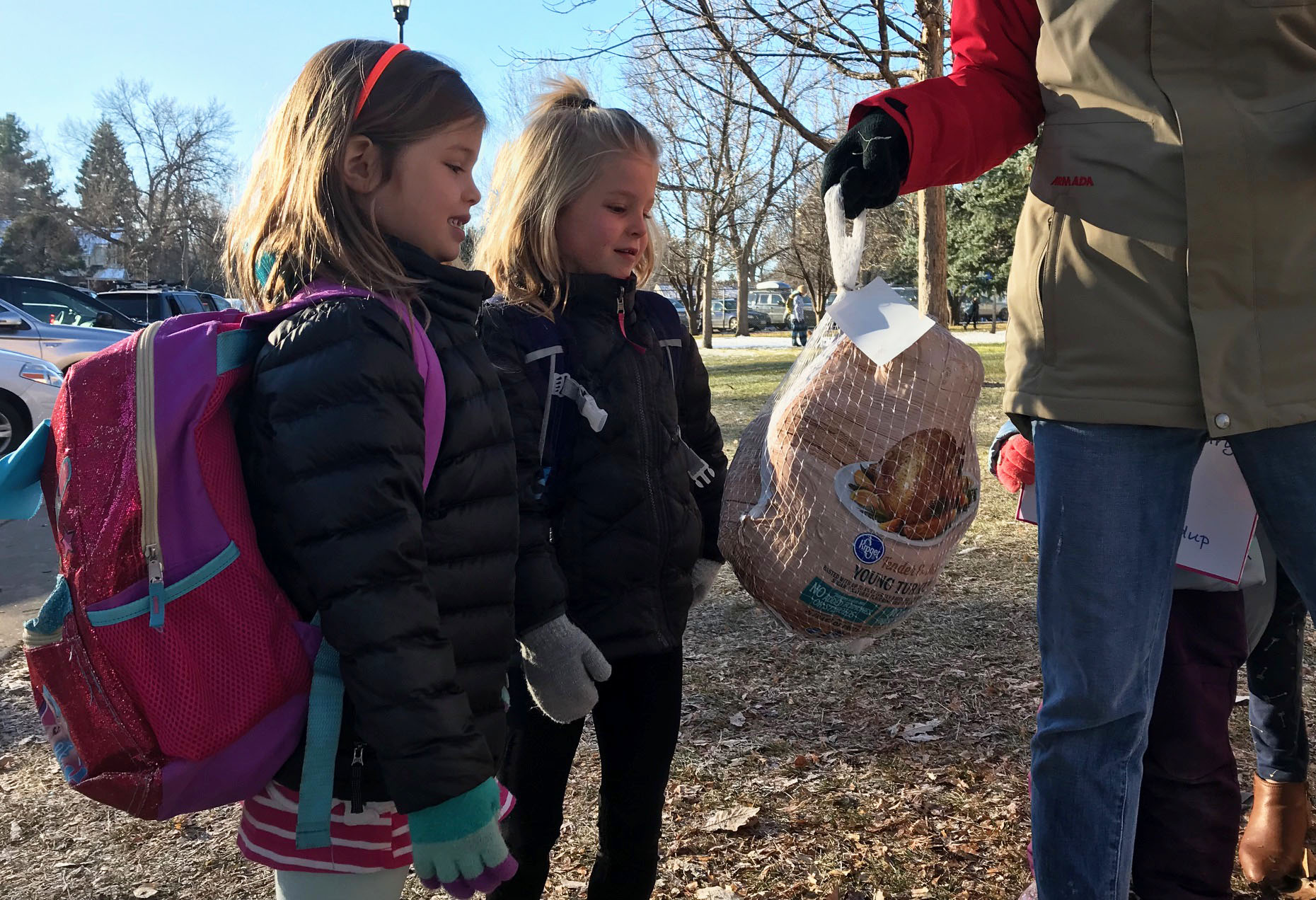 Two girls pose with a turkey they're donating to the Dunn Elementary turkey drive, part of the PSD Turkey Round Up.
