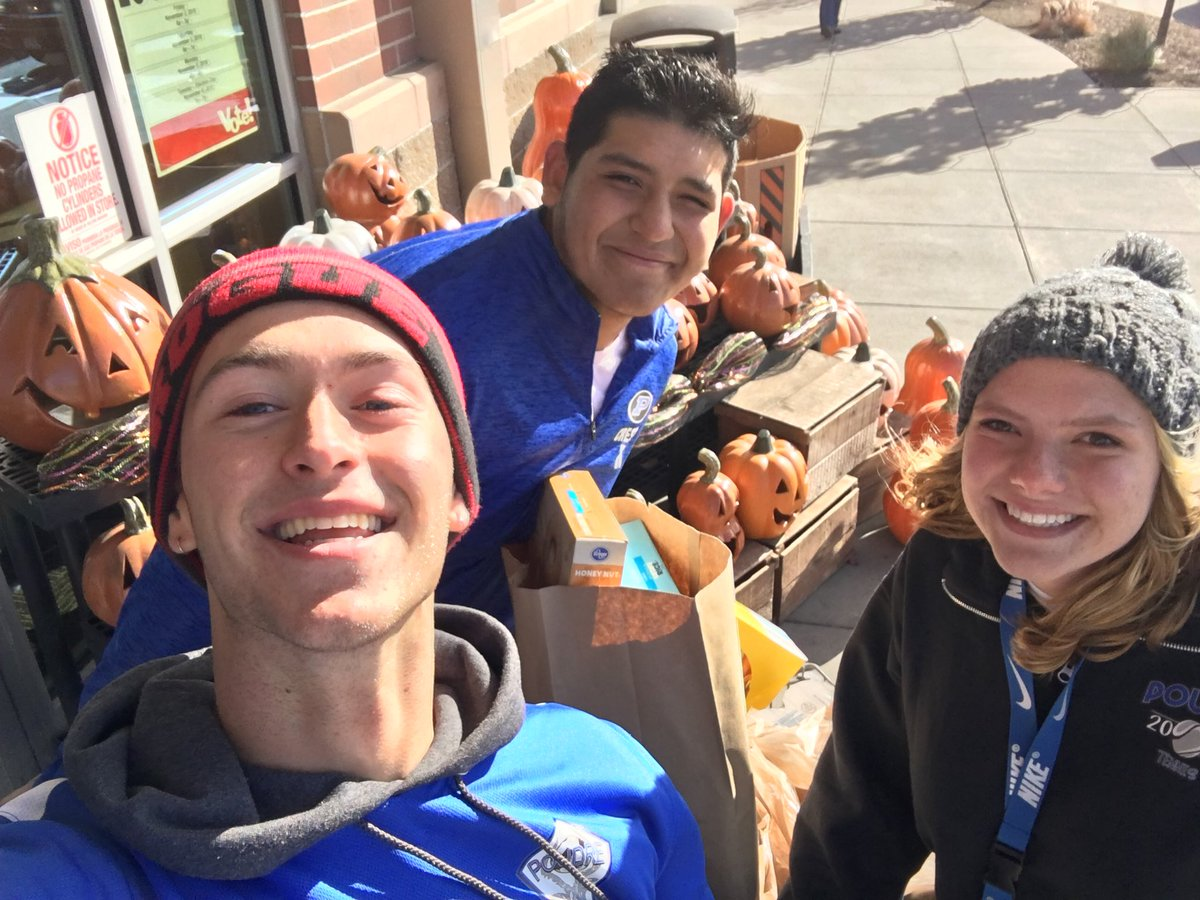 Three PHS student volunteers accept donations of food in front of a pile of pumpkins outside of a grocery store.