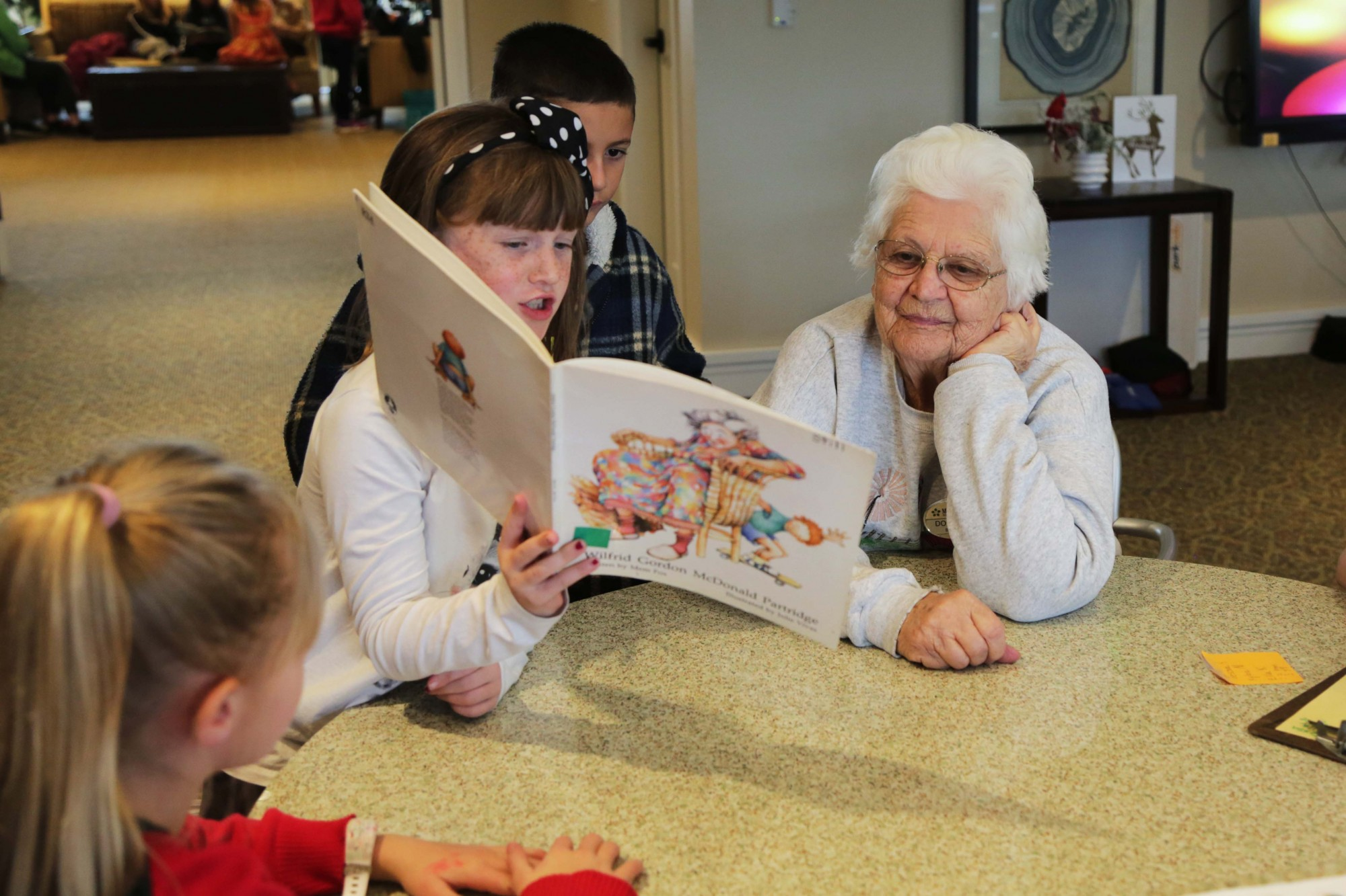 A girl from Johnson Elementary reads to a senior citizen, a resident of Morning Star Assisted Living Residential Home