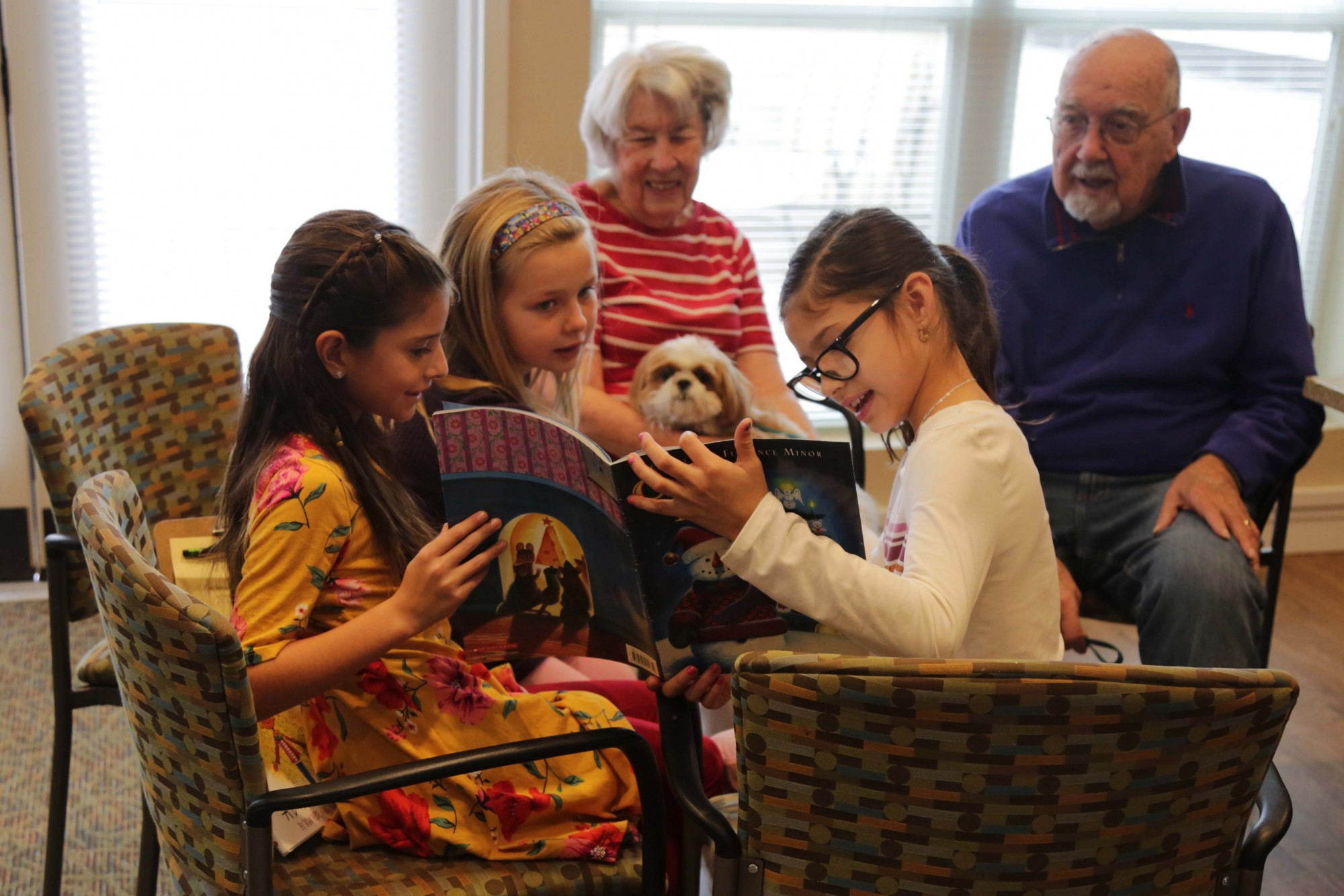 A group of Johnson Elementary students read a story to a senior couple at Morning Star Residential Home.