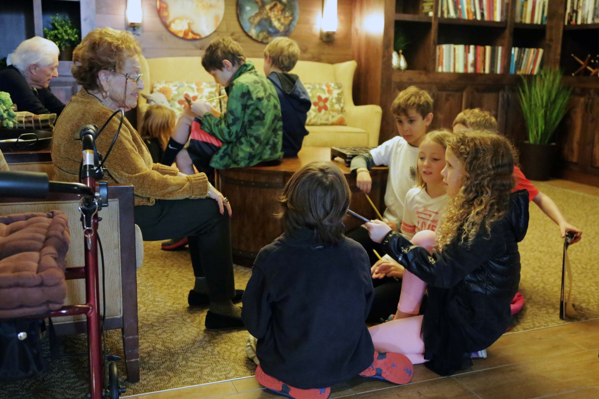 A group of Johnson Elementary students reads to a senior sitting on a couch at Morning Star Residential Home.