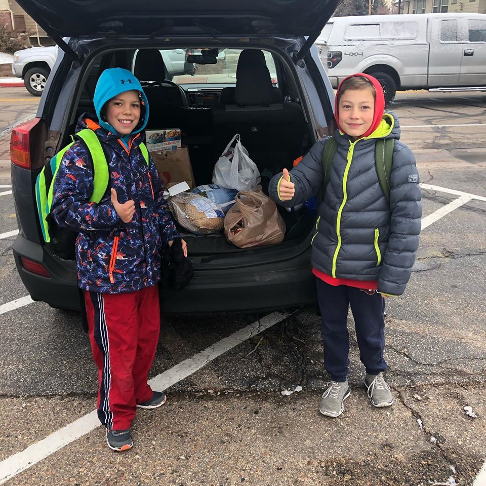 Two Bennet Elementary students give a thumbs up among donated turkeys and goods for the Turkey Roundup