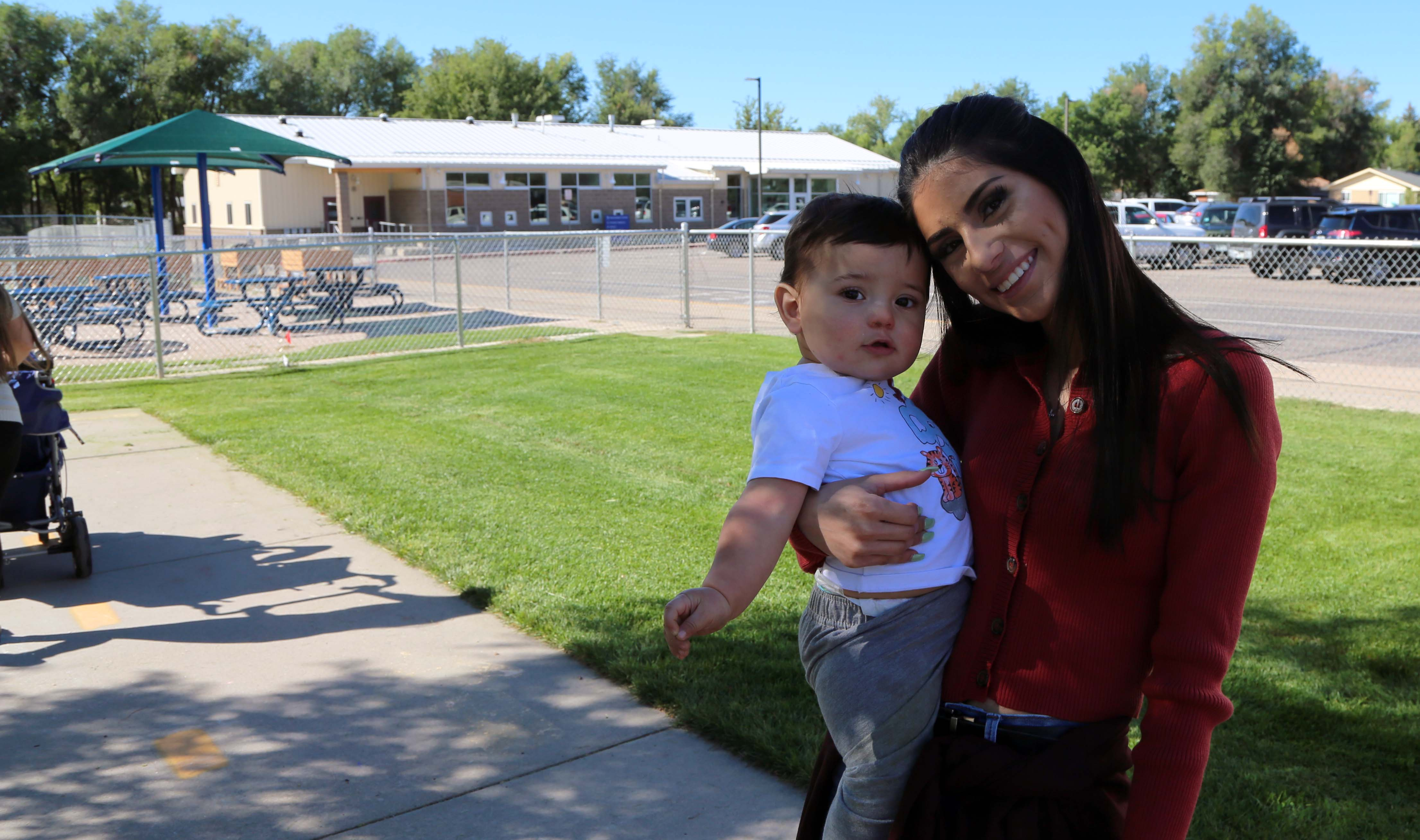 A student holds her son, who stays in a childcare center while she attends school.