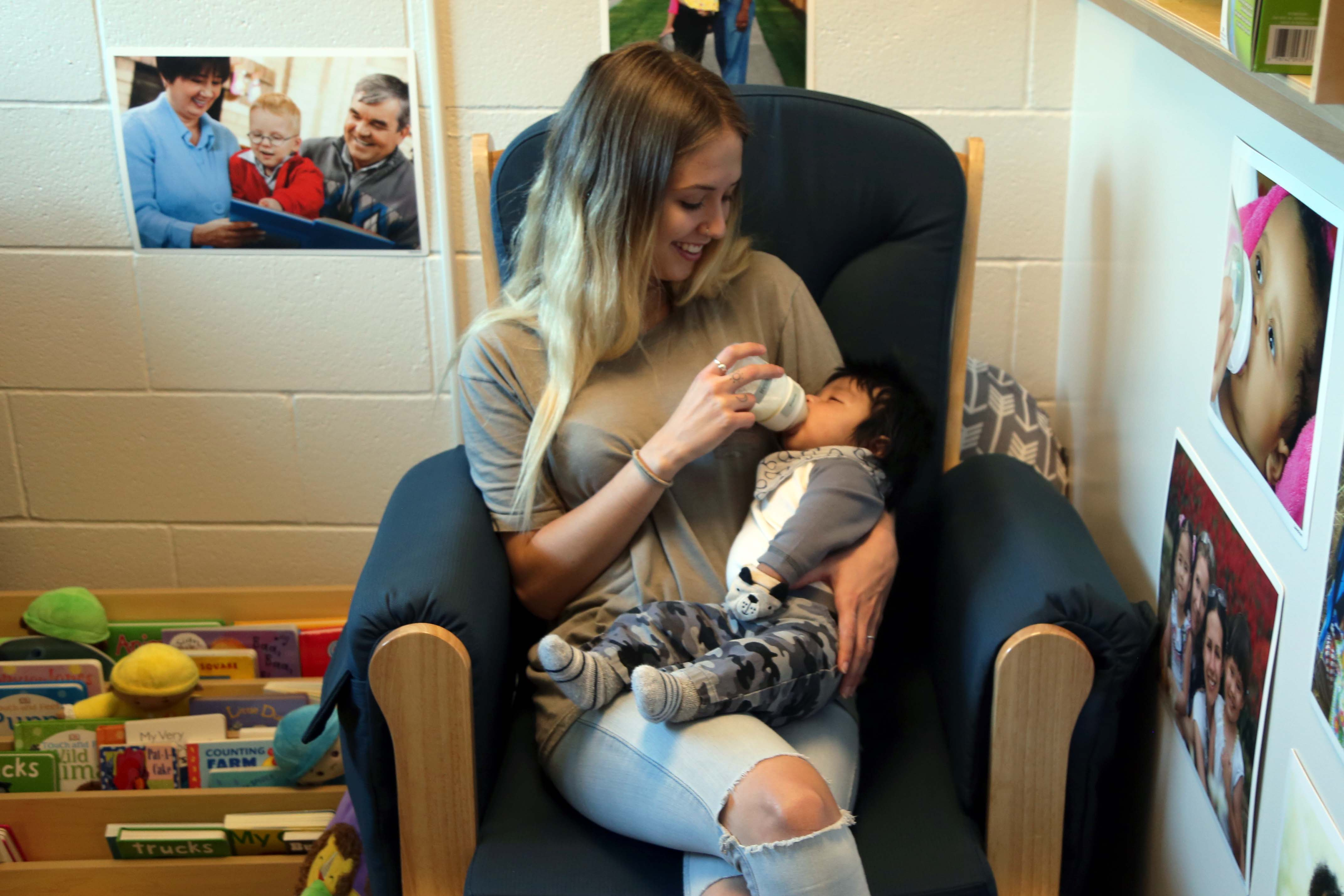 A student feeds her baby in the childcare center at the school she attends.