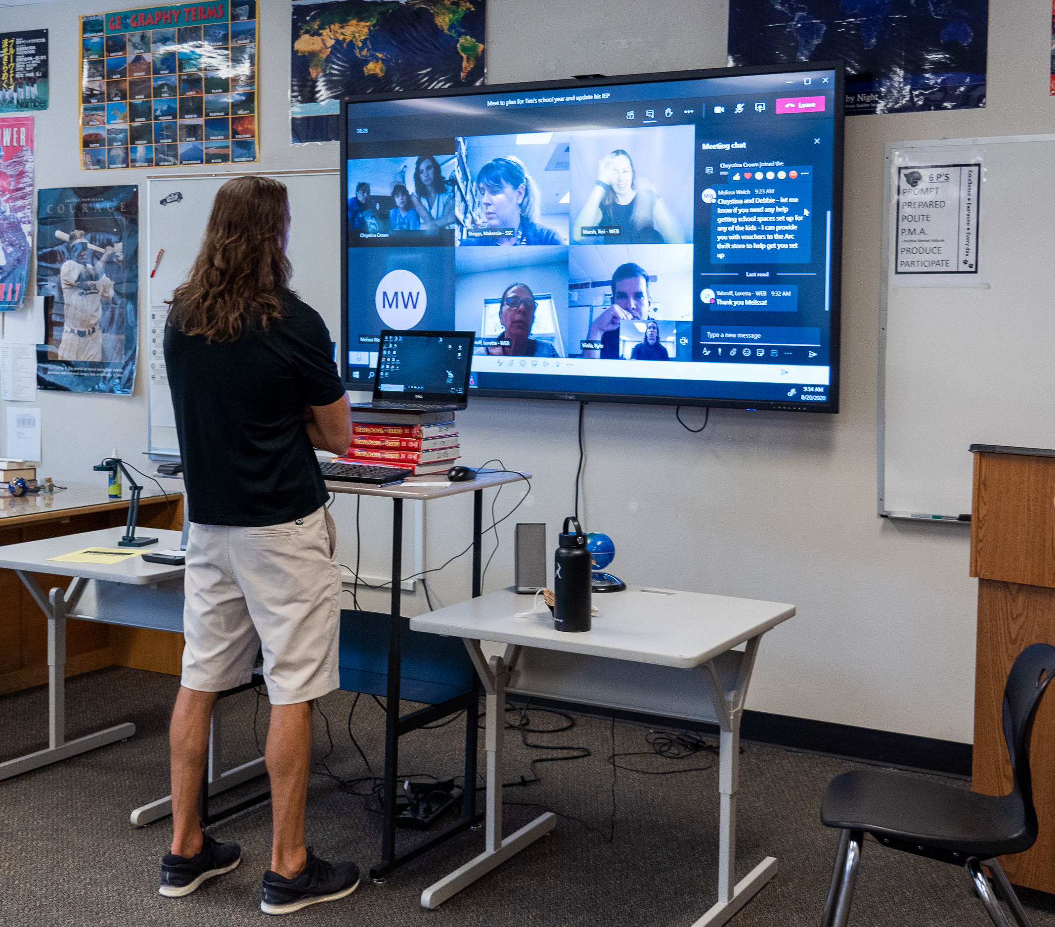 A teacher stands at his computer with a big screen showing a virtual meeting.