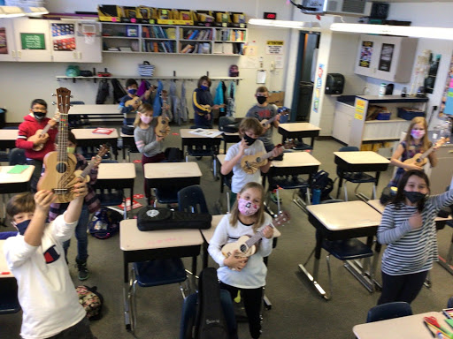 Kids in a classroom holding up their ukeleles.