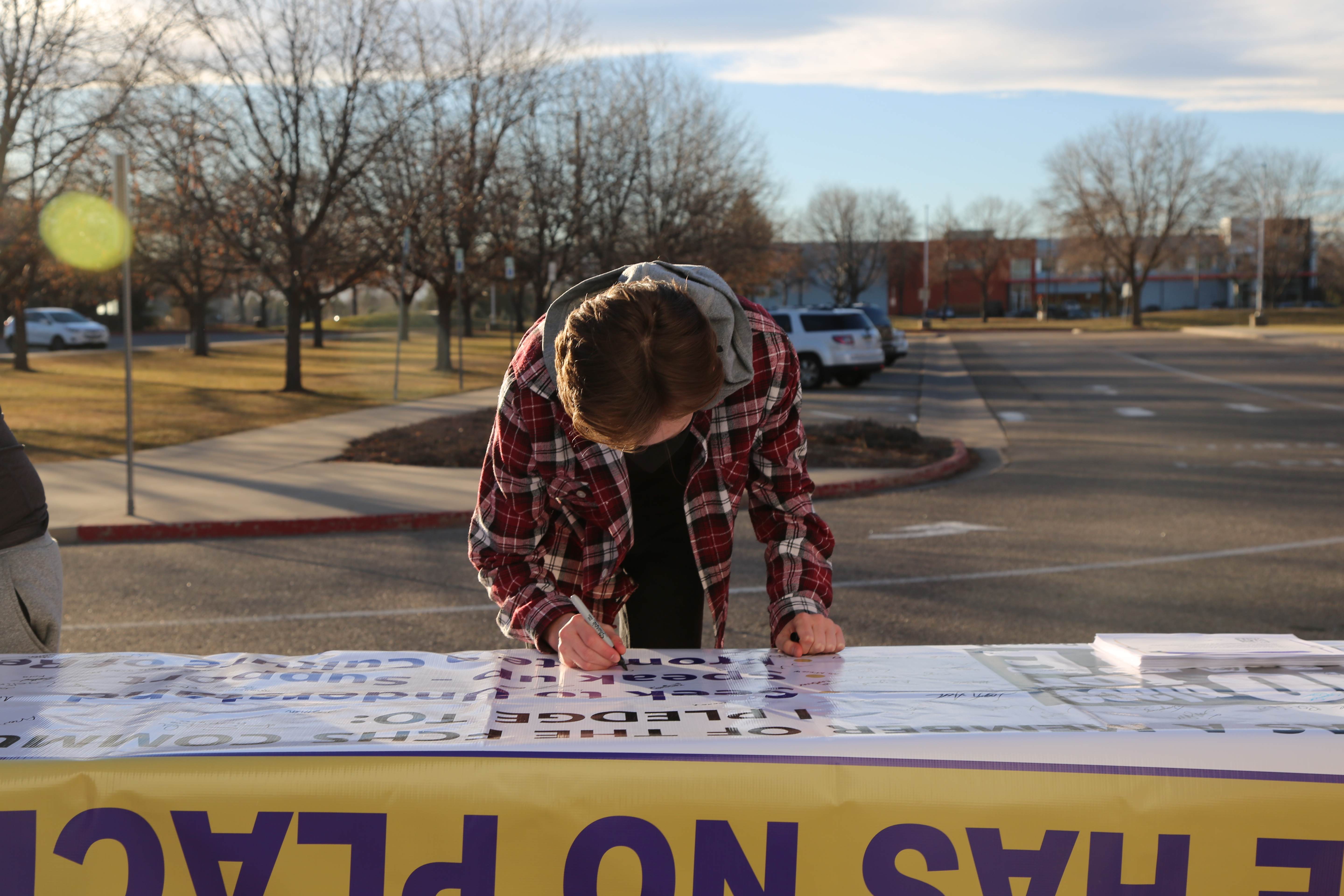 Student signing the No Place for Hate banner outside Fort Collins High School.