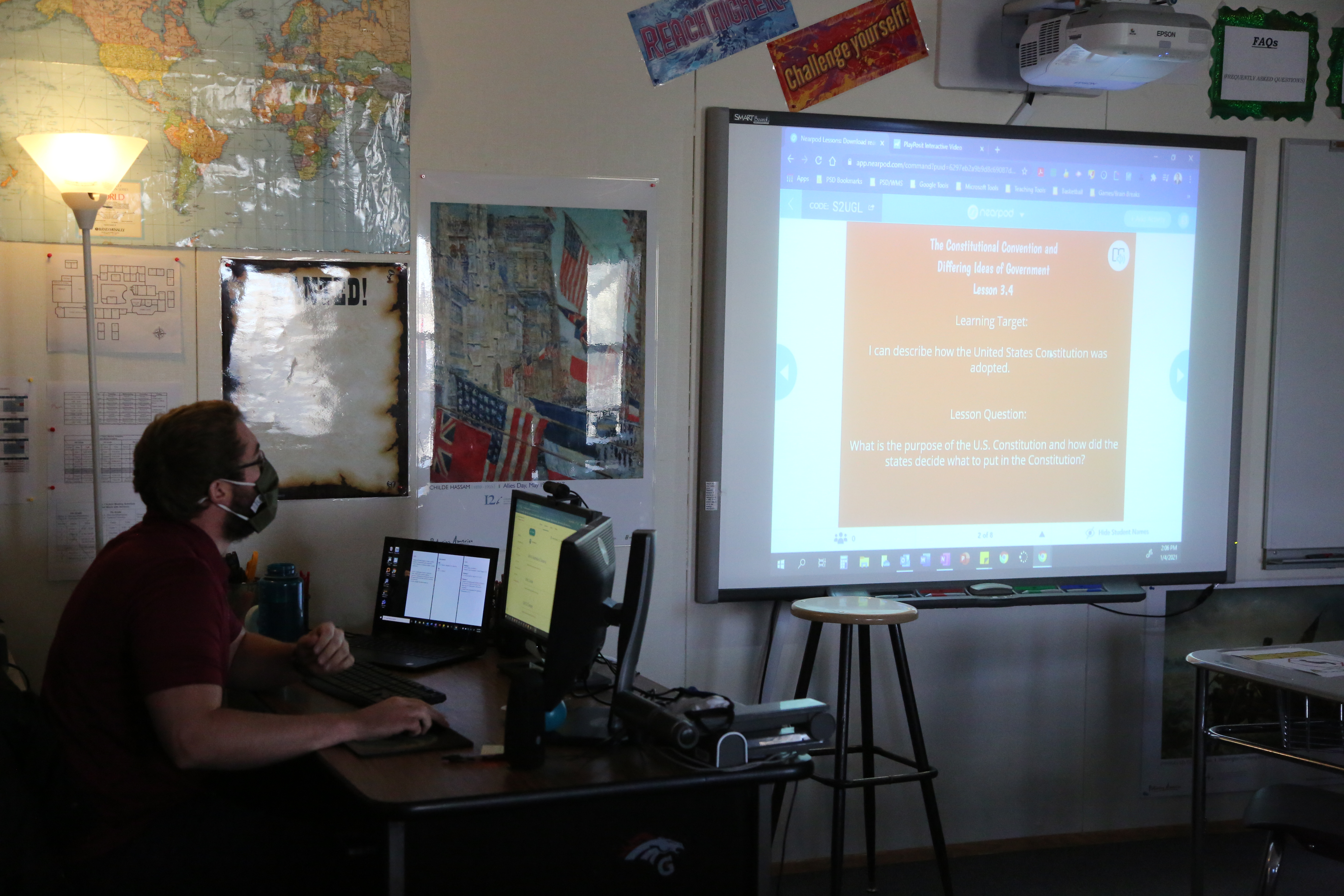 A teacher presents information online to his students from his classroom.