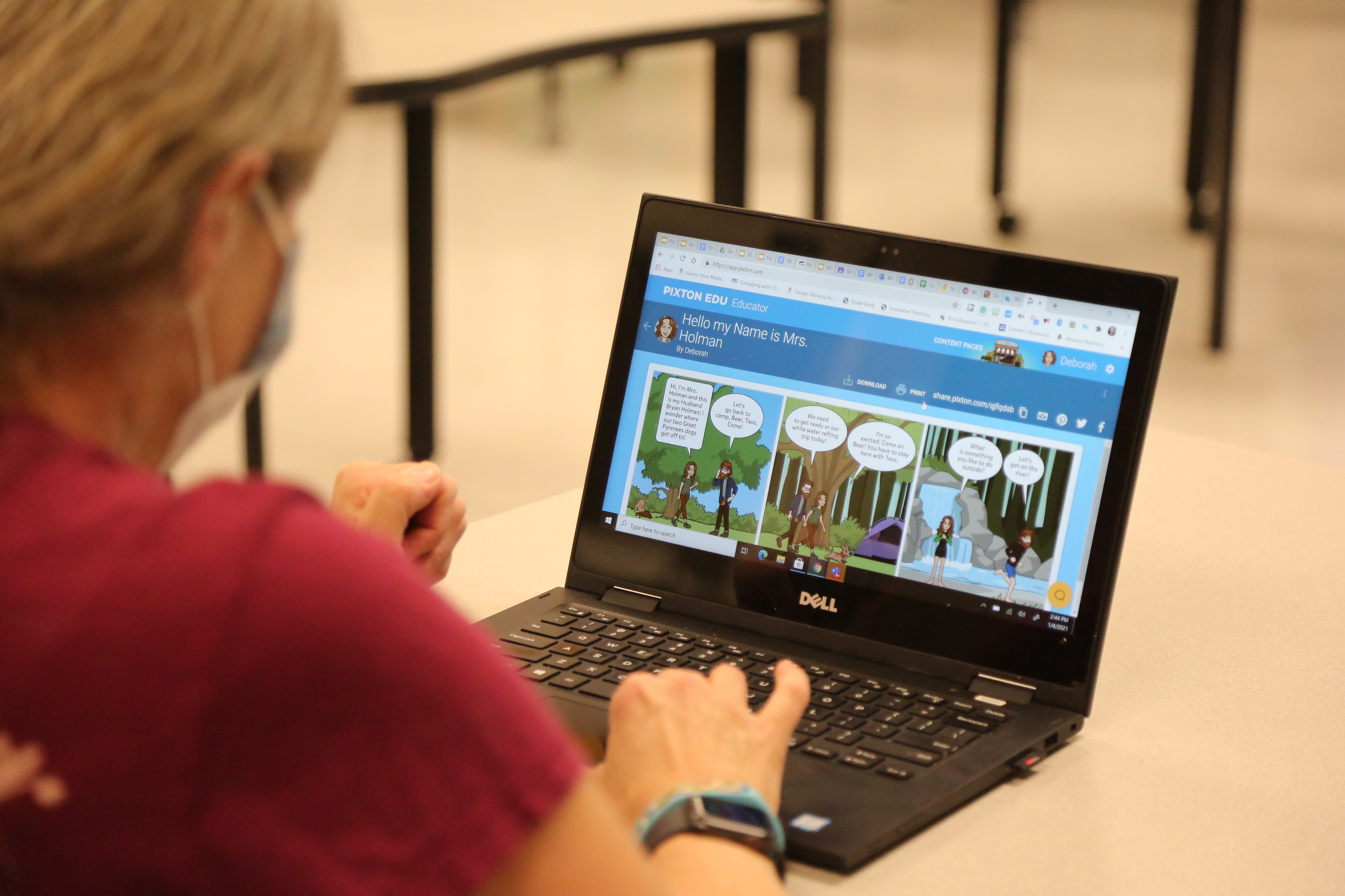 A teacher uses her laptop to present information.