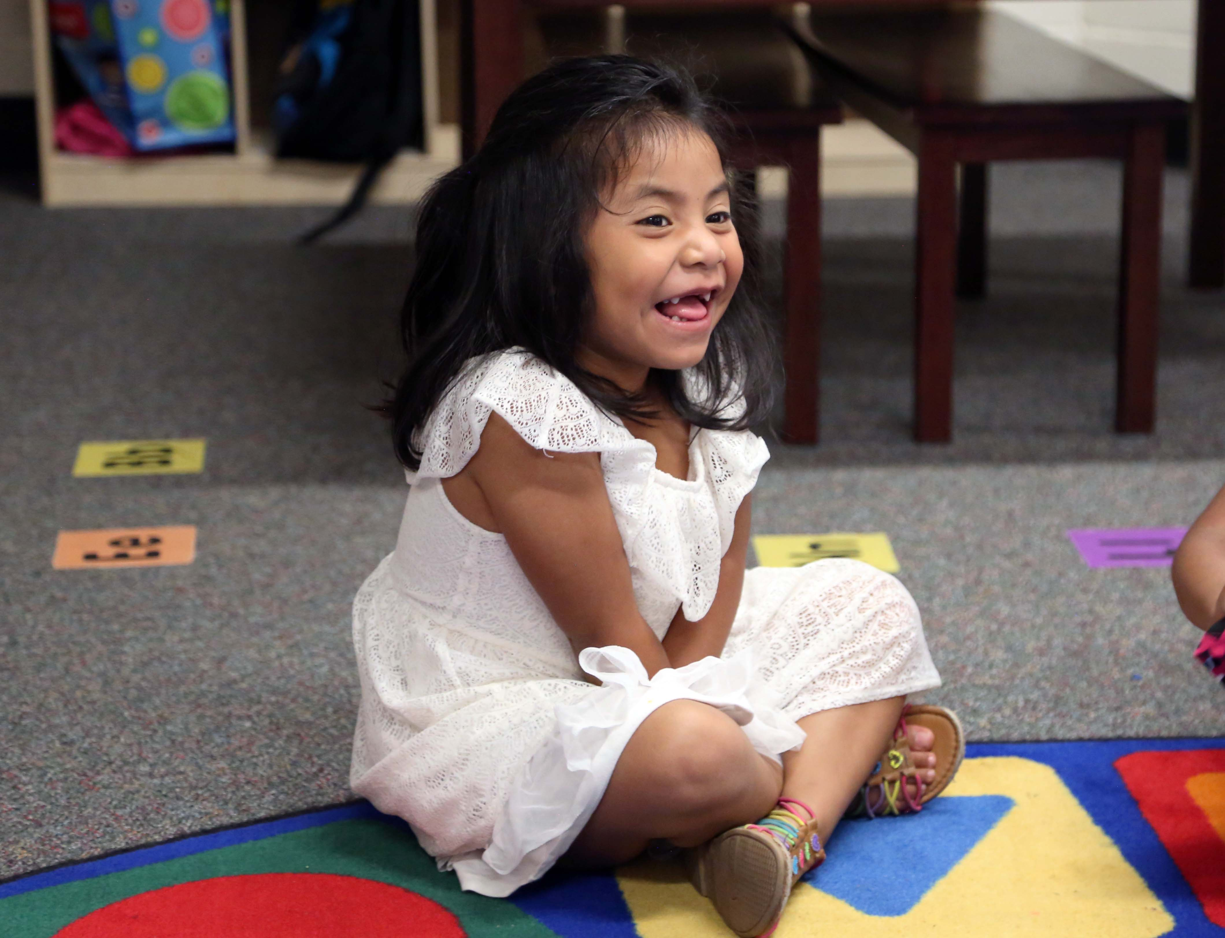 A preschool girl gives a gapped-tooth grin while sitting on the circle rug.