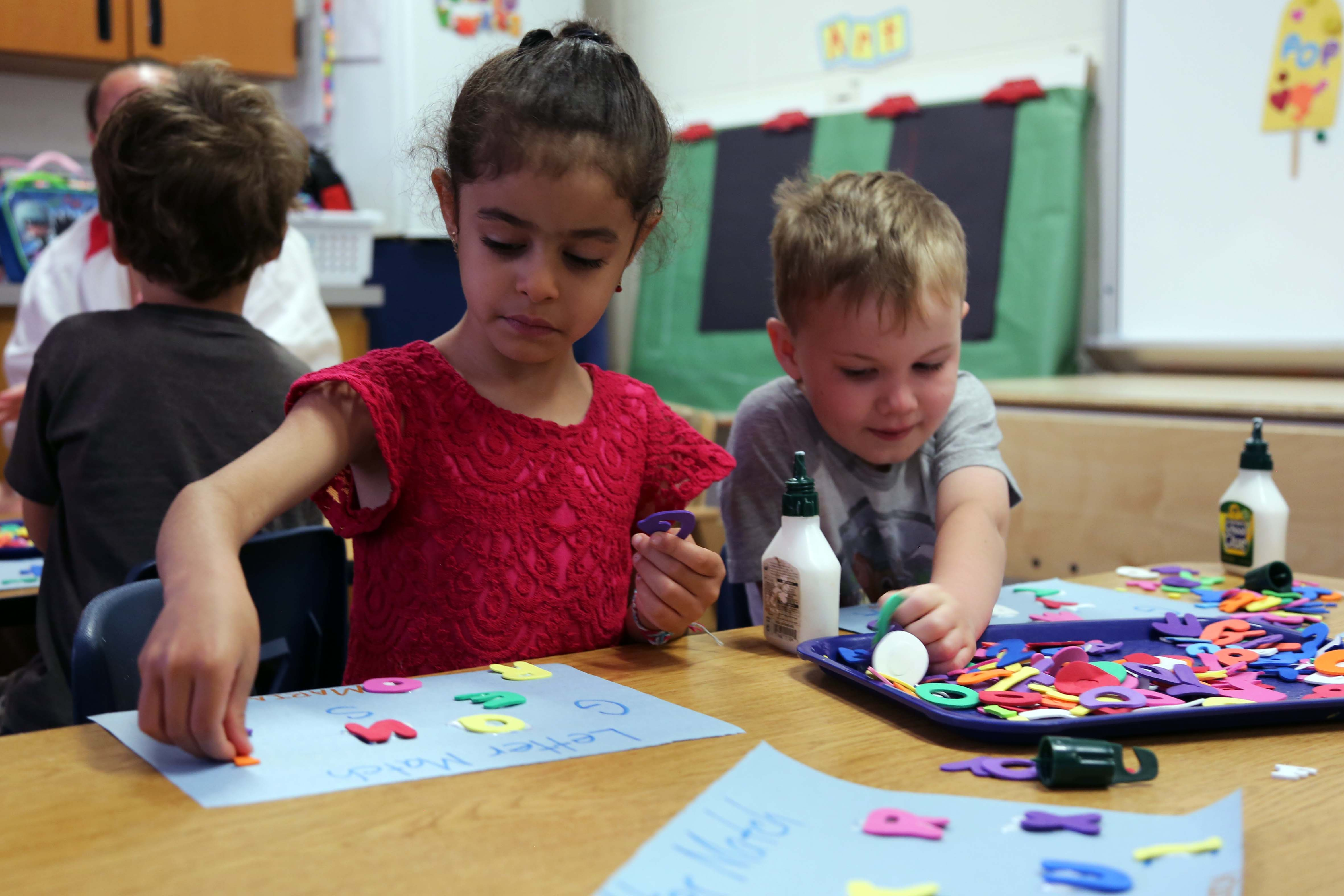 Two preschoolers play at a desk at a Poudre School District classroom.